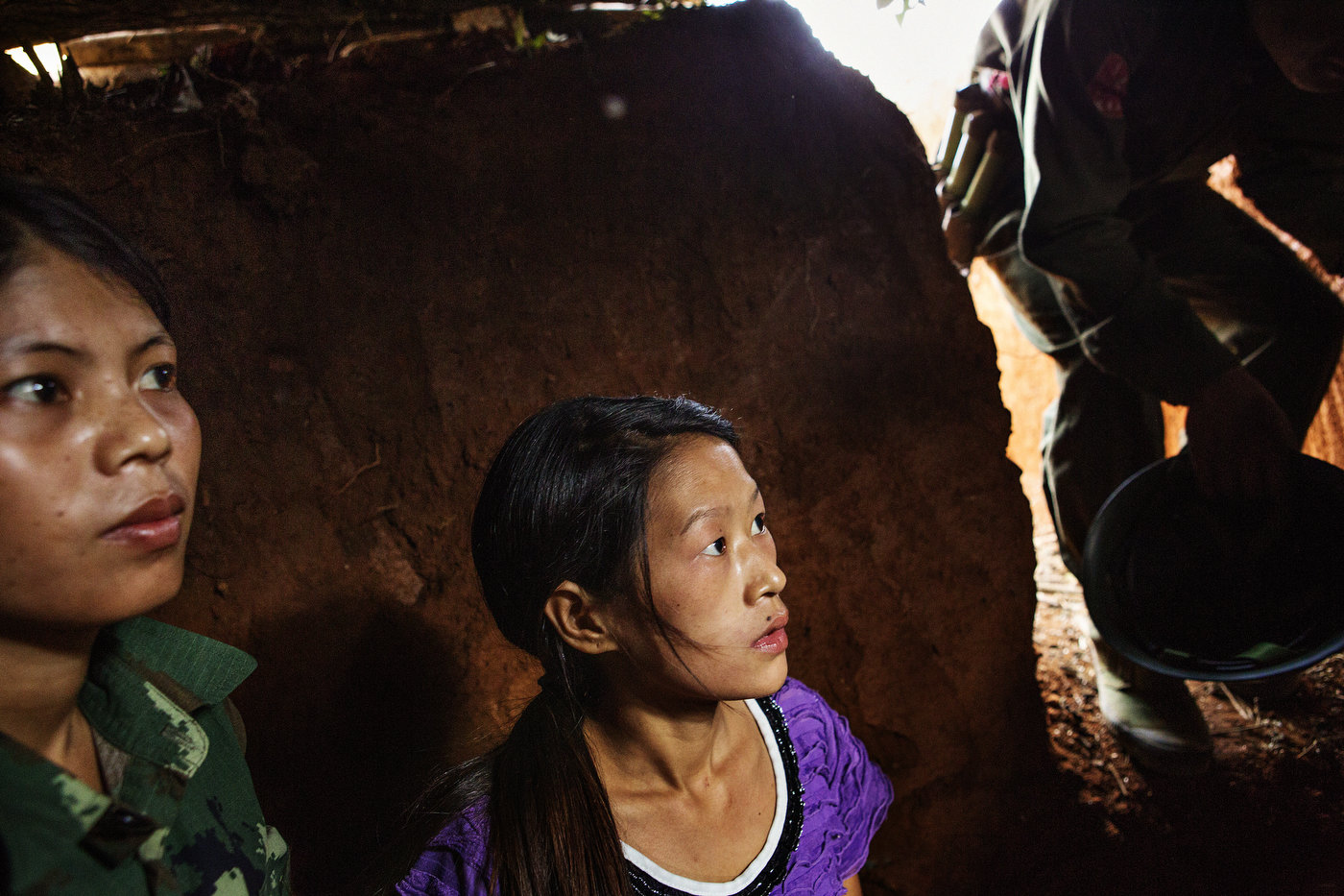 Two female Kachin Independence Army (KIA) medics take cover in a bunker as Burmese jets are approaching in the distance December 30, 2012 close to the small town of Namsangyang. In recent days, the Burmese Army has deployed helicopter gunships and fighter jets.