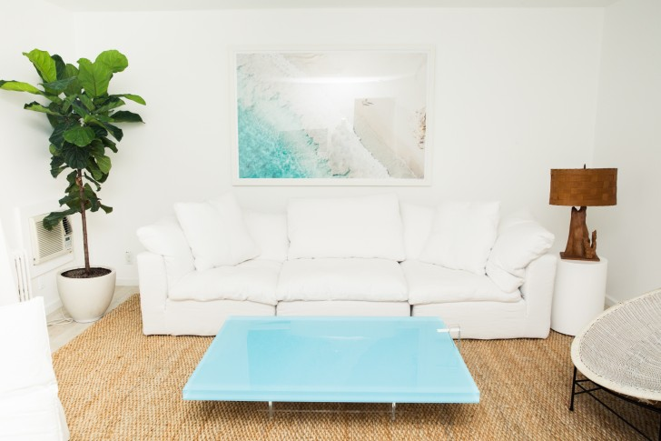 white couch, jute rug, and aqua glass coffee table