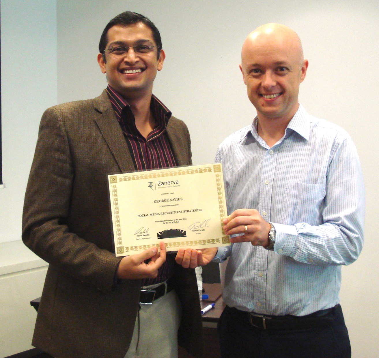 George Xavier receiving his certificate of workshop participation from  Martin Cerullo for attending the Social Media Recruitment in Dubai