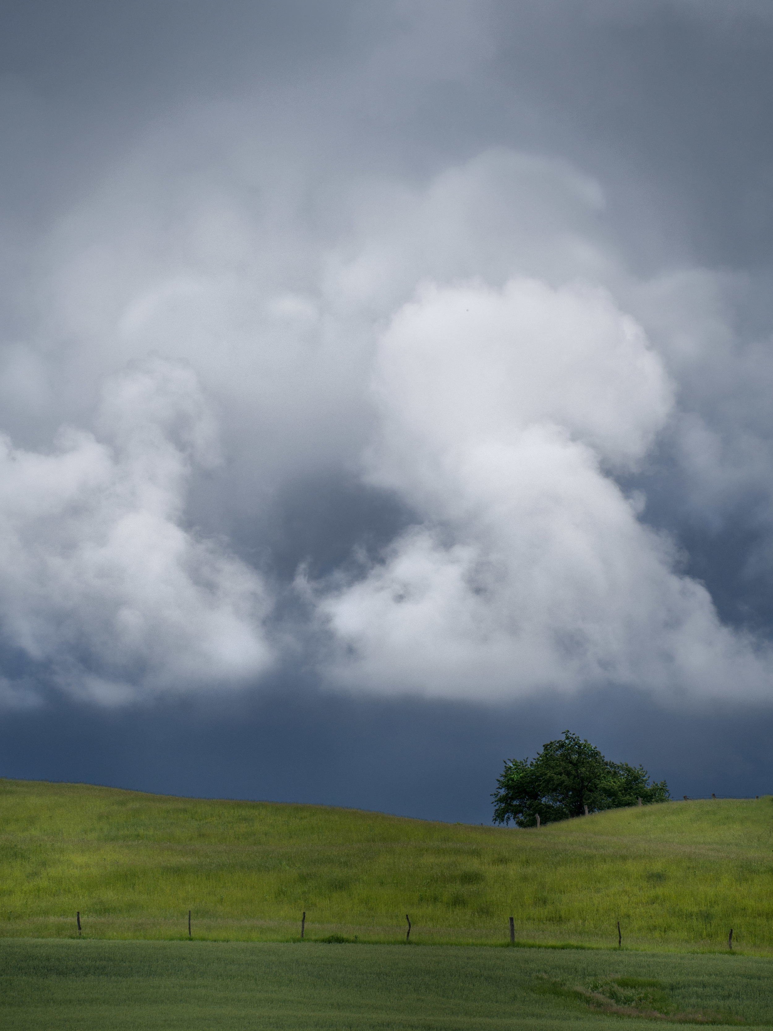 Dark skies,white clouds, and lush green countryside make for a contrast explosion.