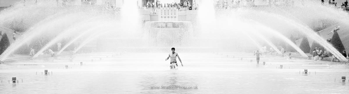 A bather wades through the fountains of the Jardins du Trocadéro, Paris, France.