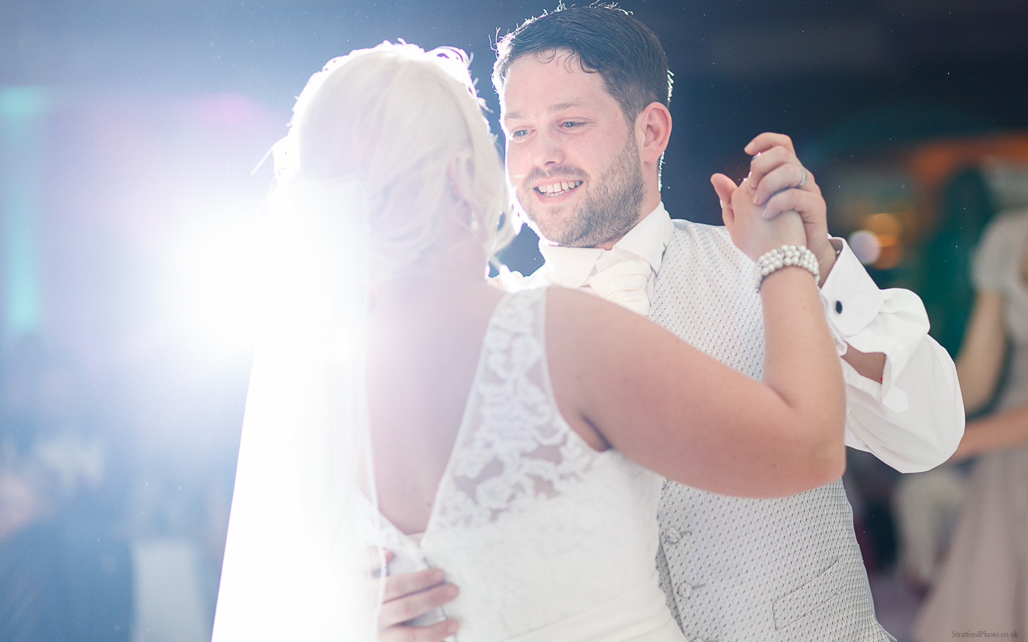 Bride and Groom share a romantic first dance in dramatic cinematic light
