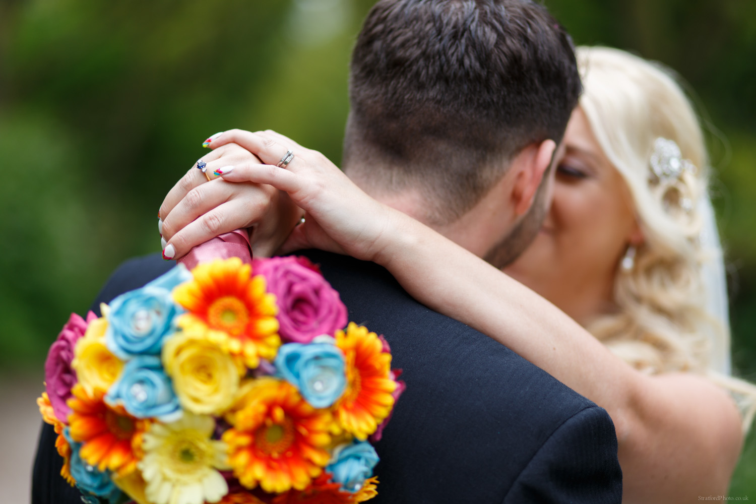 Bride and Groom share a romantic moment alone in the woods surrounded by nature and green as bride clasps vivid colourful bouquet behind groom neck