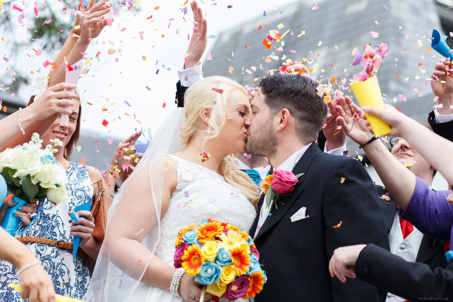 Bride and Groom kiss as guests throw colourful confetti exciting their ceremony at Mercure Chester North Woodhey House