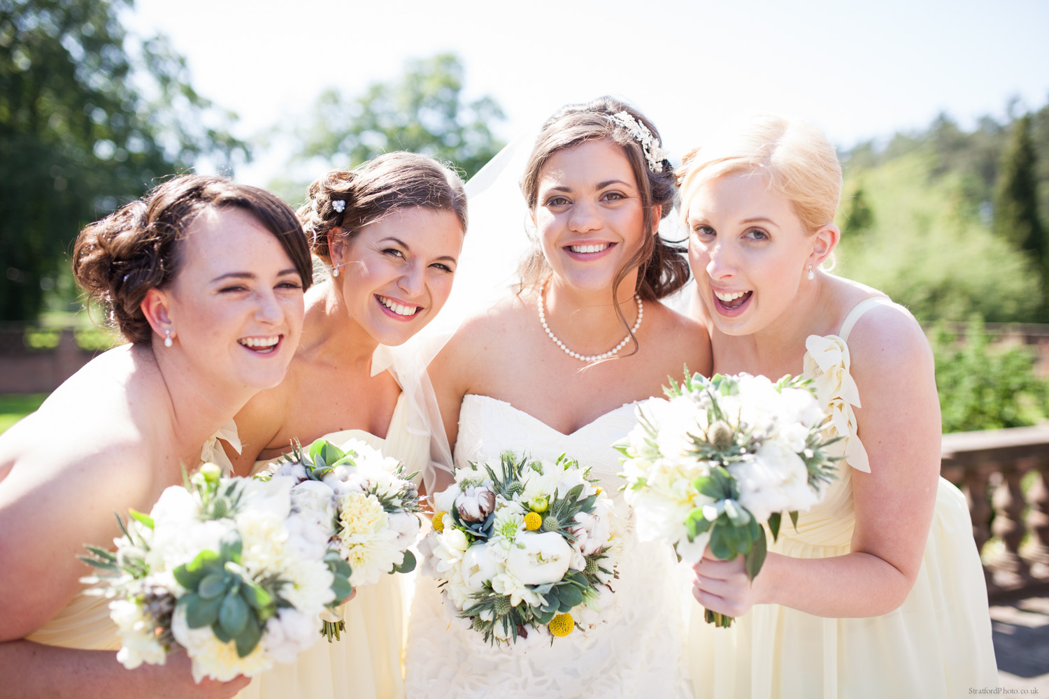 A bride and her three beautiful bridesmaids dressed in lemon yellow laugh in the summer sun at Inglewood Manor.jpg