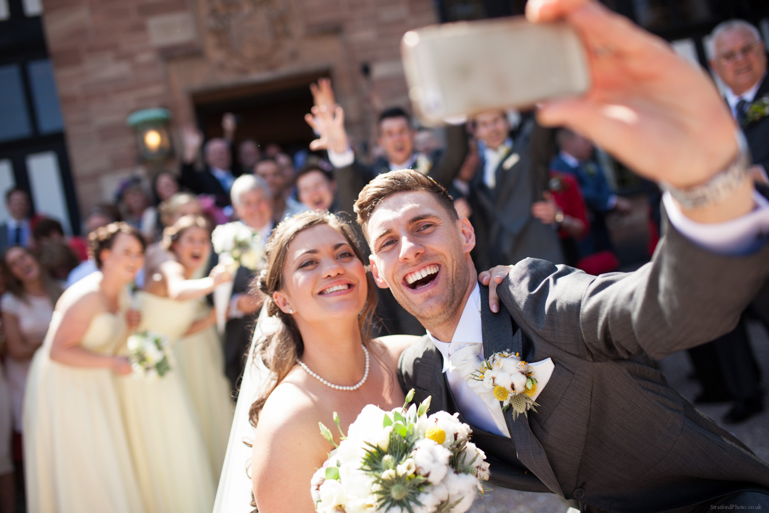 A young bride and groom take a selfie in front of their wedding guests in teh summer sun at Inglewood Manor