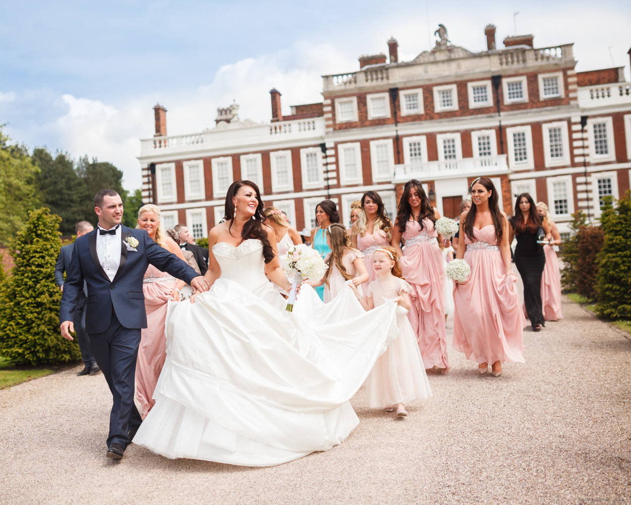 A bride and her groom walk from Knowsley Hall to the gates with their grand bridal party in tow