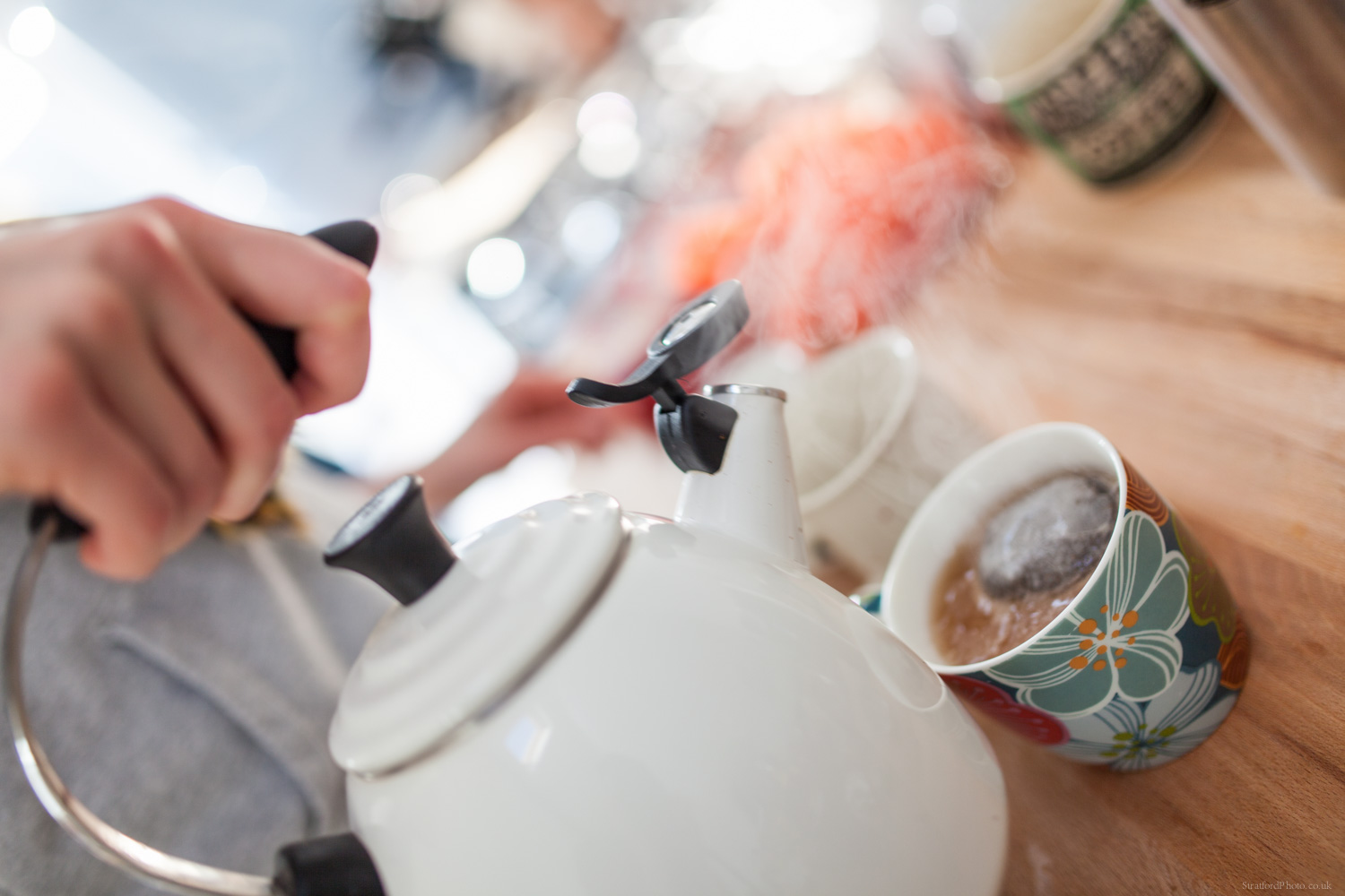 Tea is poured into a teacup from a teapot