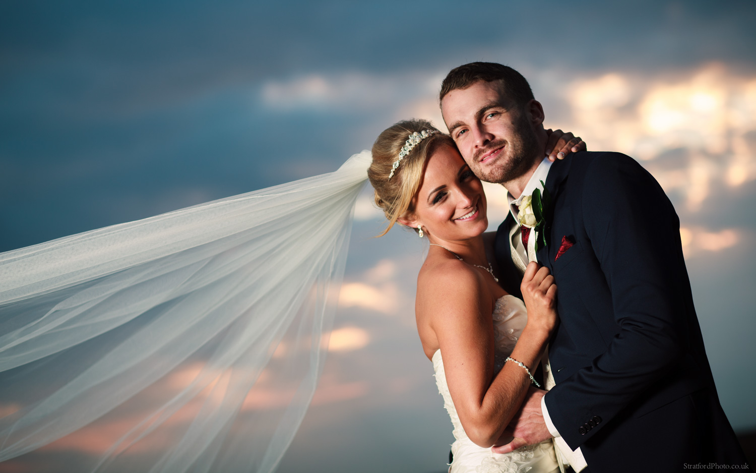 A bride and groom embrace on their wedding day before a setting sun in New Brighton at the Leasowe Castle