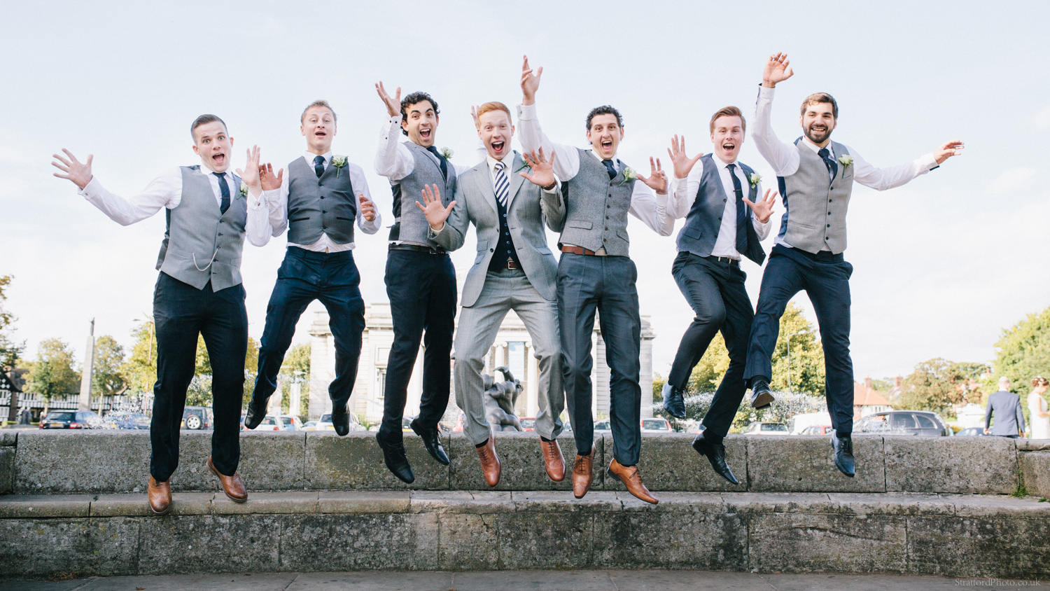 A groom and his groomsmen jump in the air at Port Sunlight Wirral