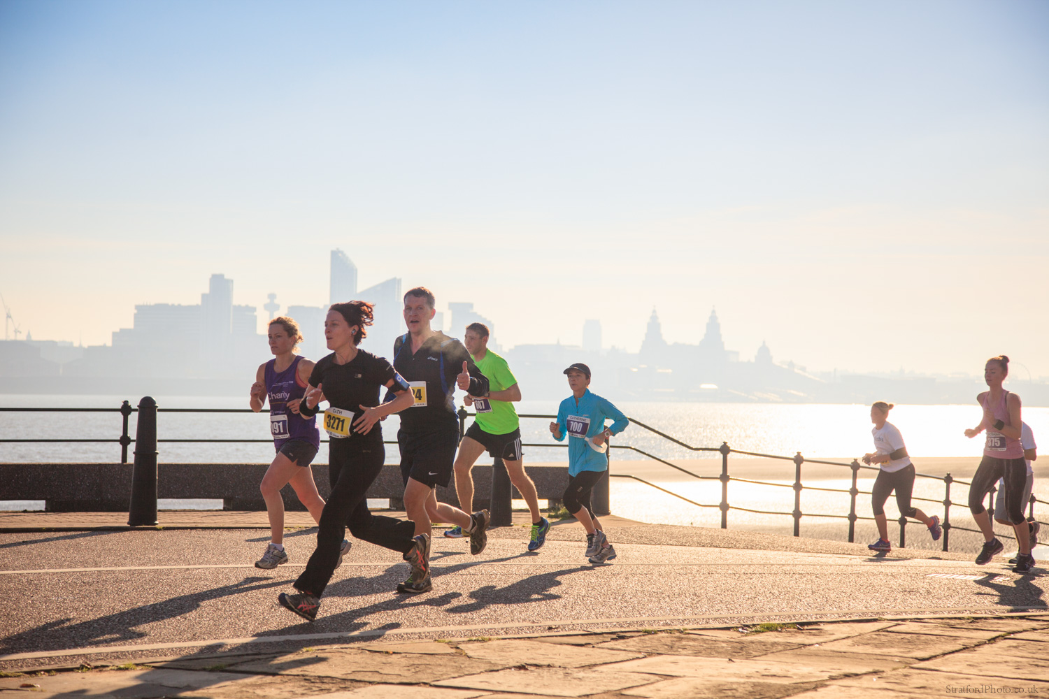 Runners in the 2014 BTR Wirral Half Marathon run along New Brighton promenade before Liverpool majestic skyline as the bright morning sun hits the river Mersey.jpg