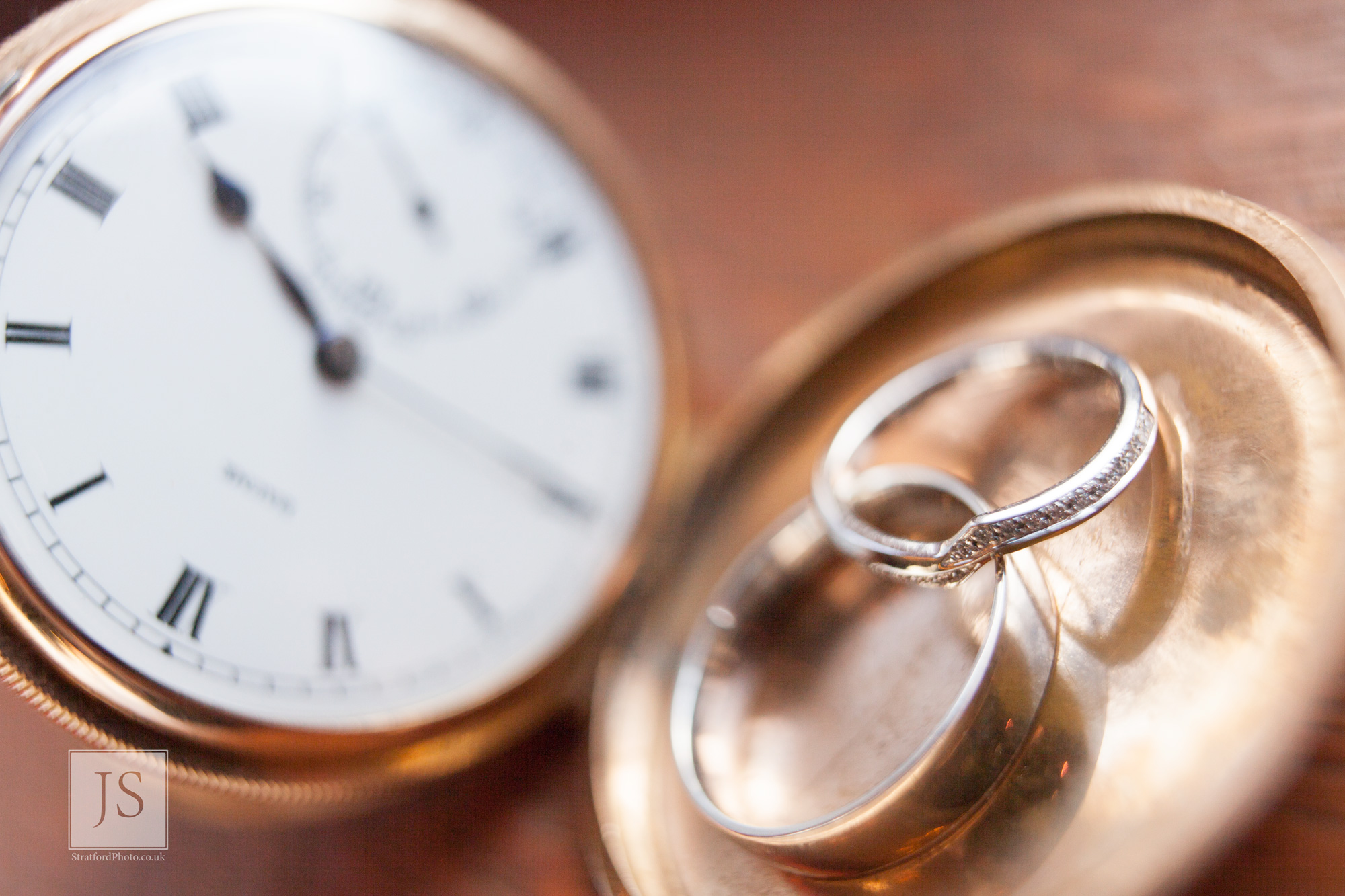 two wedding rings sit in the clasp of a gold fob watch