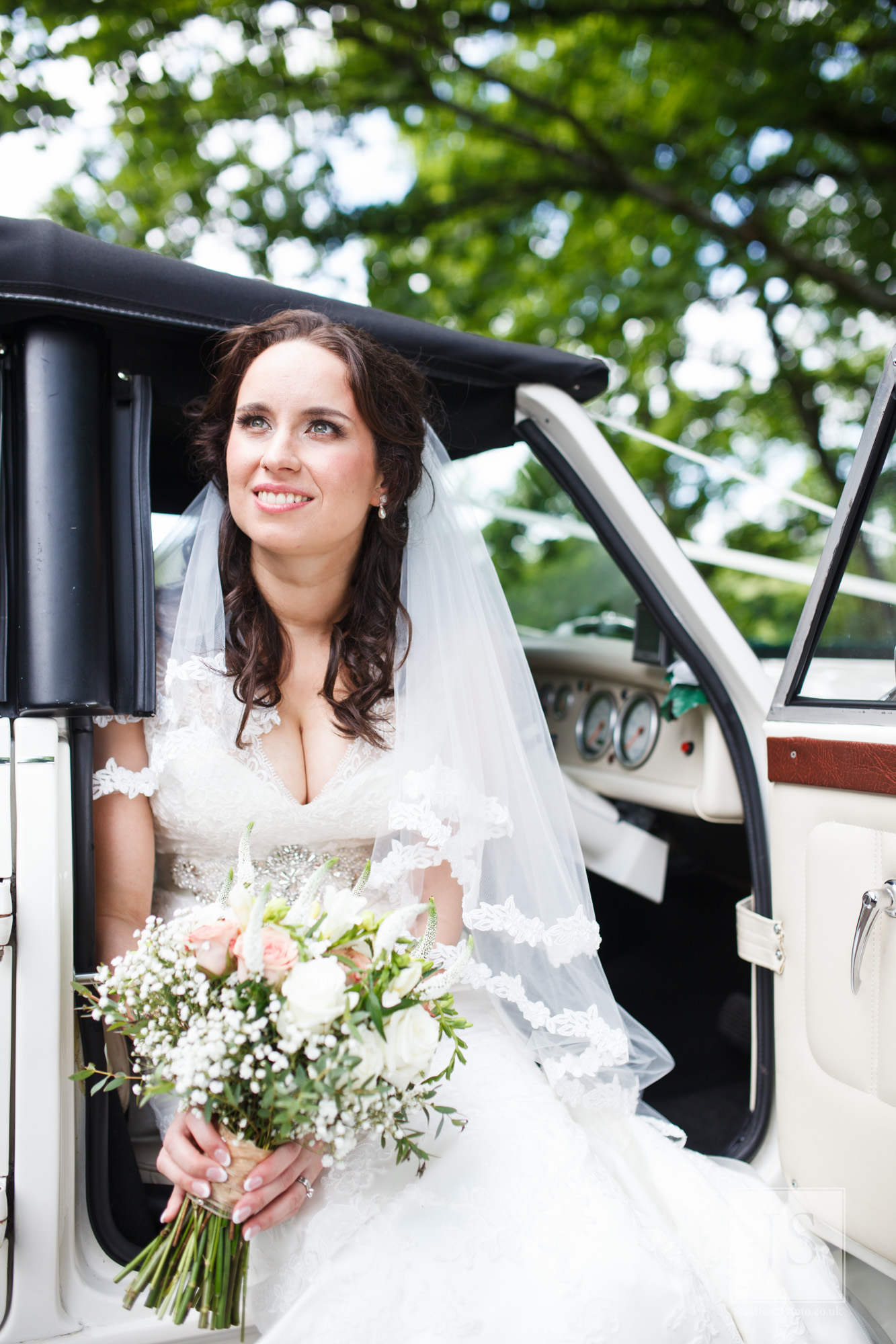 A bride perrches on the seat of her Bentley wedding car.jpg
