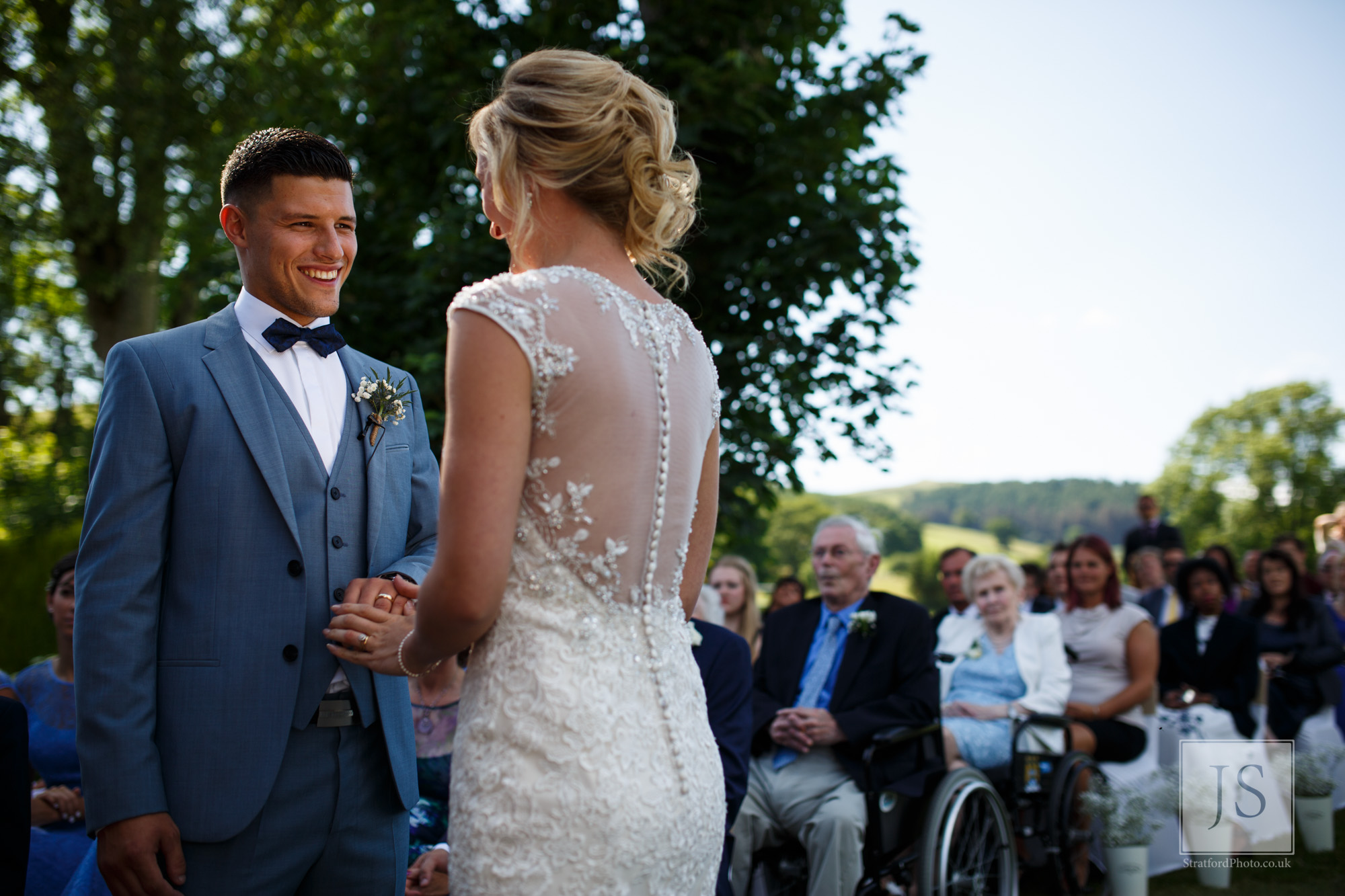 A groom smiles at his beautiful bride with the Welsh mountains behind.jpg