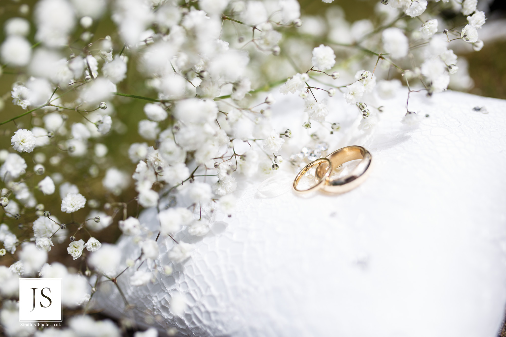 Two wedding rings sit on a cushion waiting for their bearers.jpg