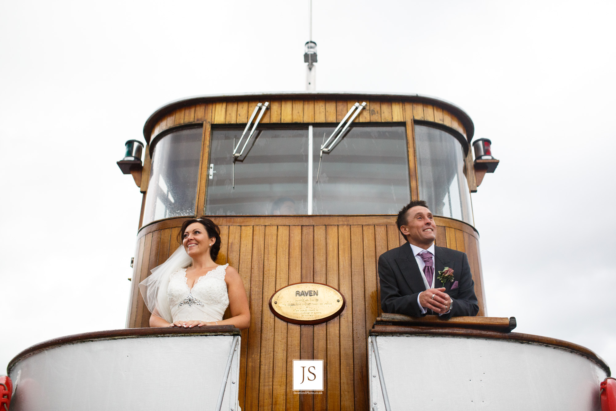 A bride and groom look out from the bridge of a Lake Ullswater steamer boat.jpg