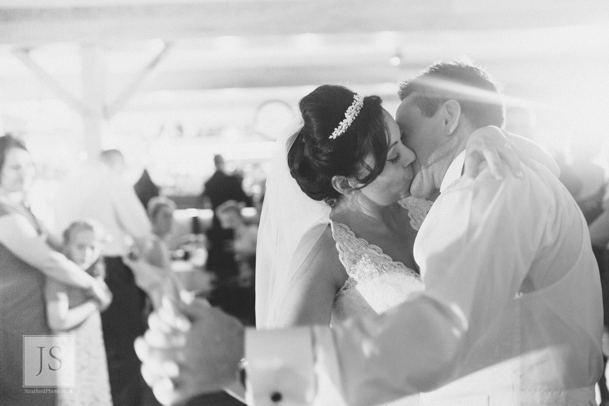 A bride and groom kiss passionately during their first dance.jpg