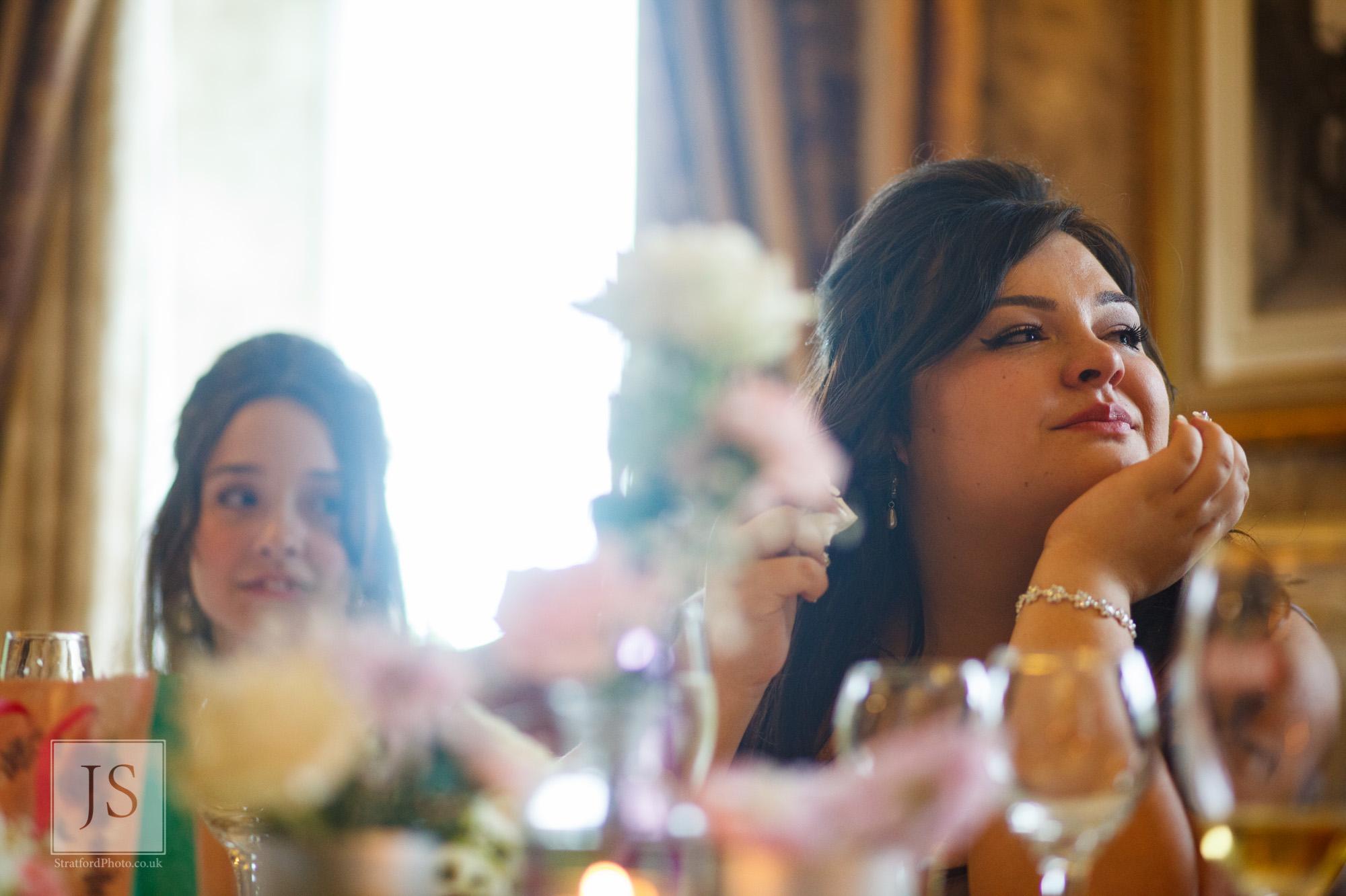 An emotional bridesmaid listens to a speech.jpg