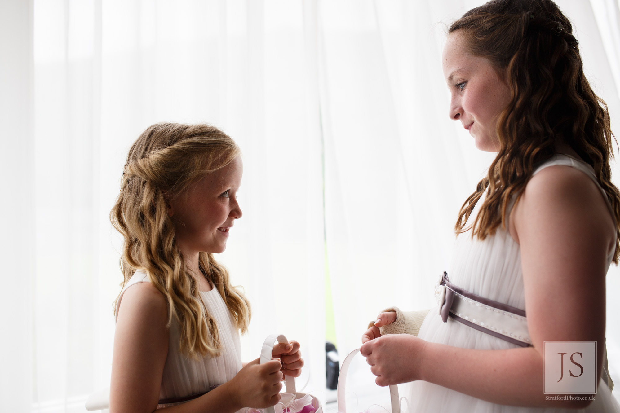 Two beautiful flower girls smile at each other in window light.jpg