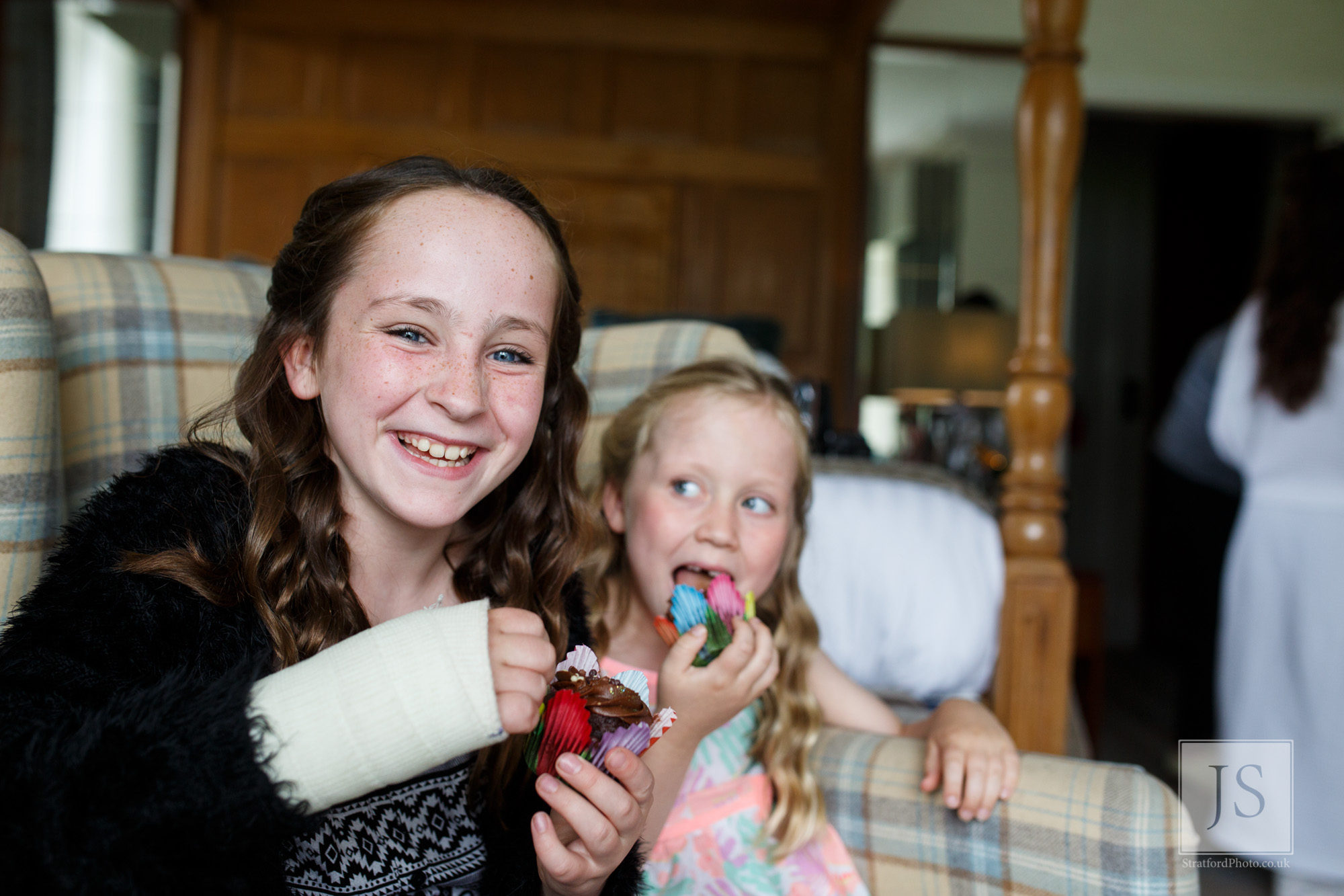 Two beautiful young girls enjoy a cupcake on the morning of a wedding.jpg