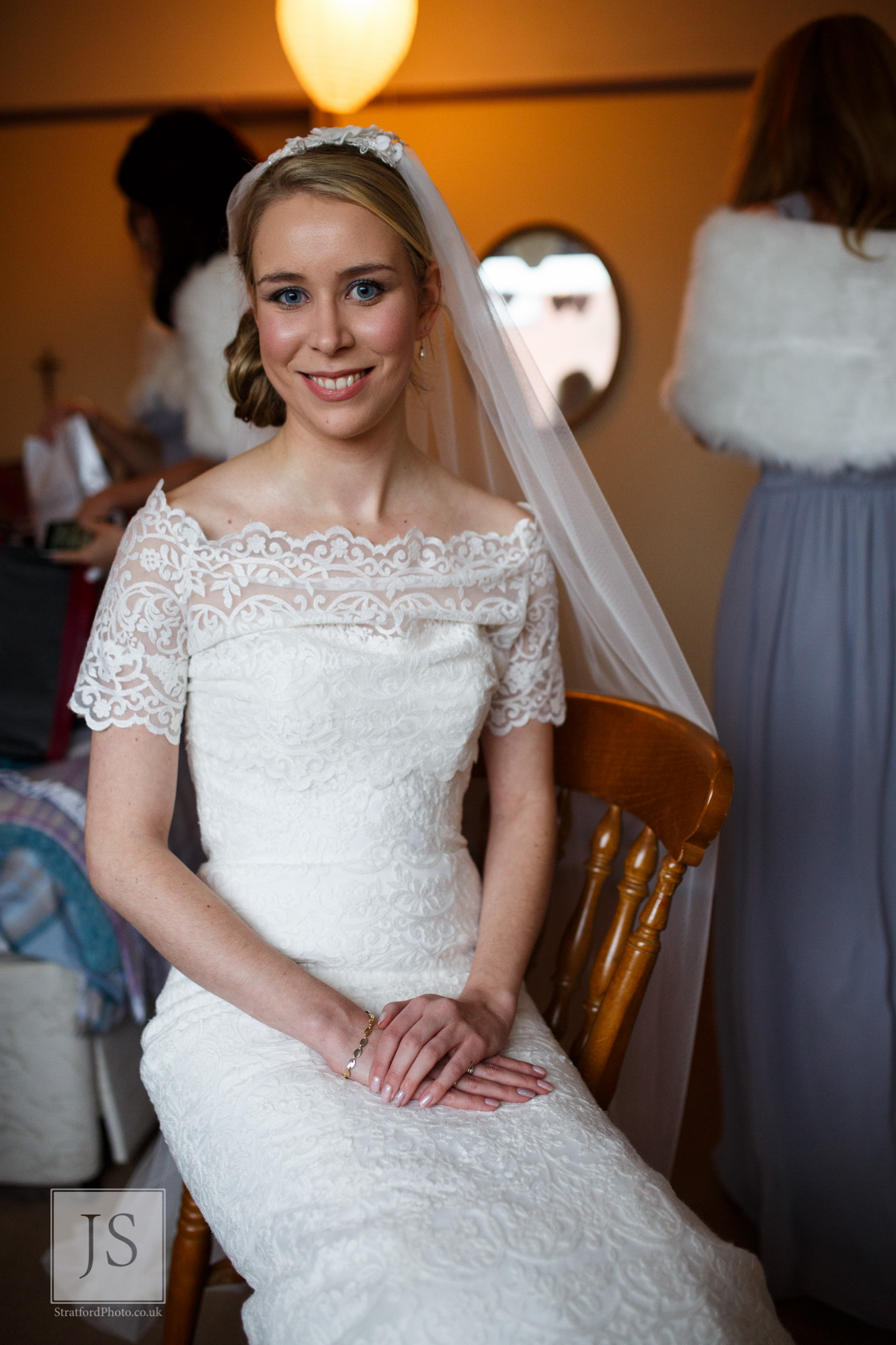A bride sits happily waiting for her car to arrive.jpg