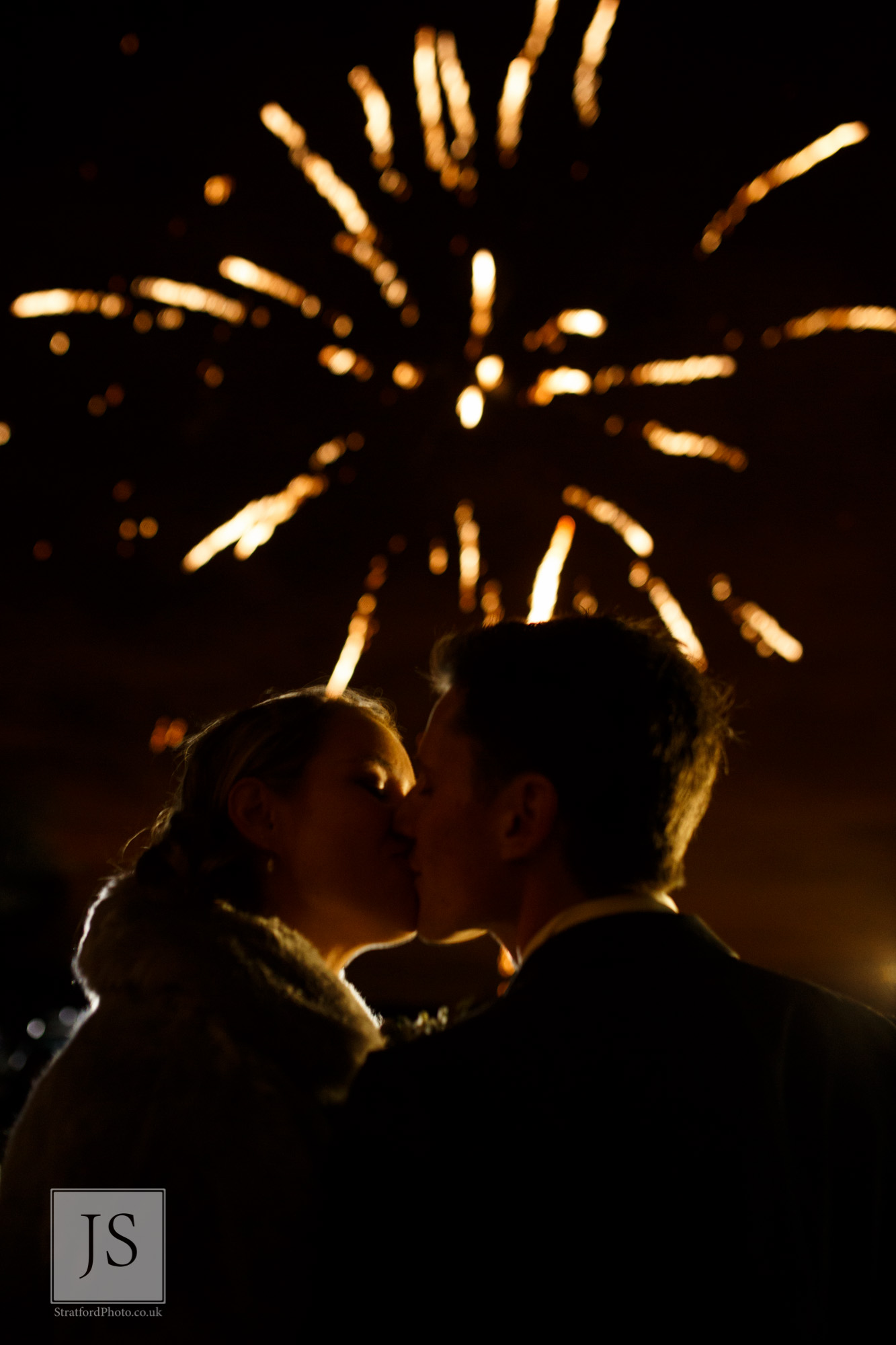 A bride and groom share a kiss before some fireworks.jpg