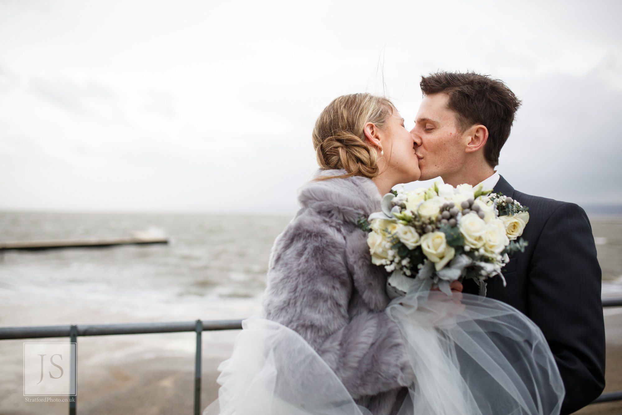 A bride and groom kiss by Marine Lake in Hoylake during Storm Desmon.jpg
