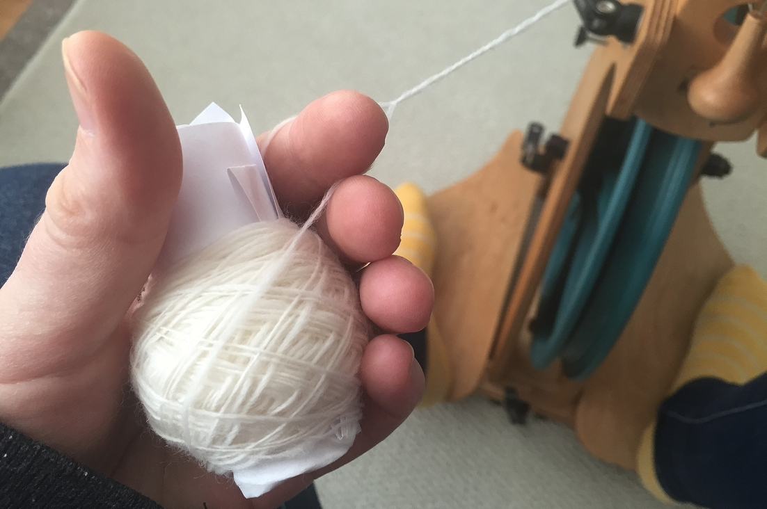 A rolled up piece of paper makes it so much easier to to ply yarn from a center pull ball. No tangles!