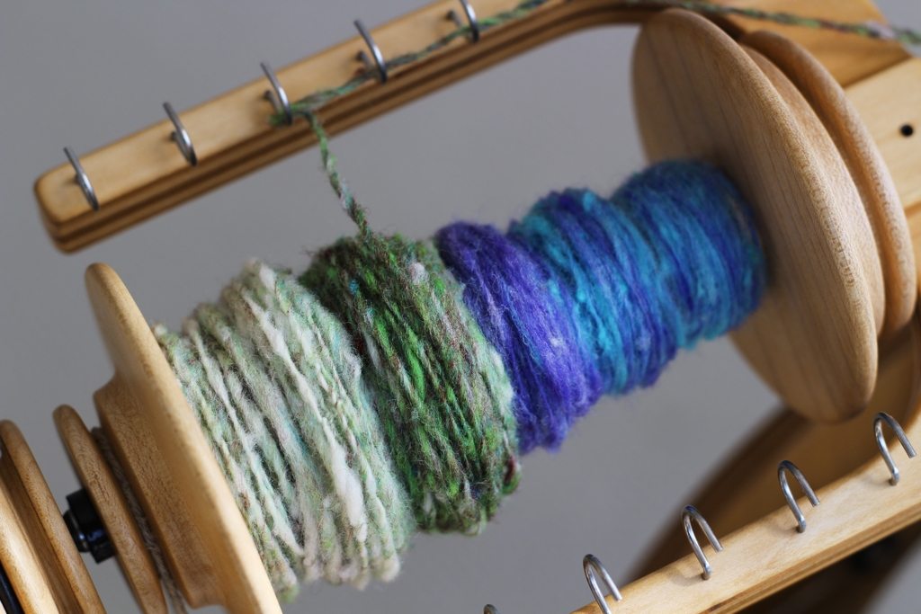 The blue and purple is what the single looked like when using the first drafting method. The green and white used the second drafting method. | Spinning Noro Rainbow Roll Part 1 - withwool.com