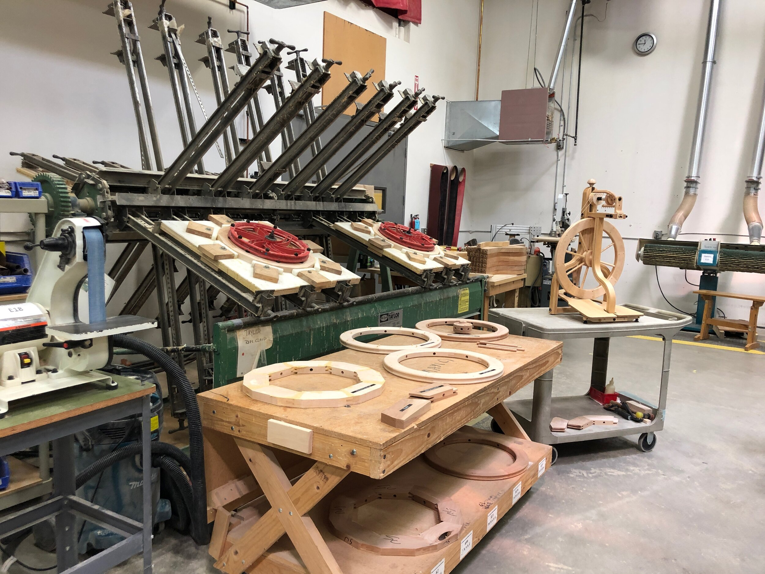 The machine used for making wooden wheels, a table showing wheels at various steps in the process, and a finished wheel on display.  Celebrating Schacht's 50th Anniversary || withwool.com  #schacht50years