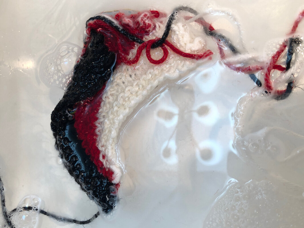 A close up view of a red, white, and black knitted swatch soaking in the sink.  Sideways Swatching || withwool.com  #knitswatch #darkmatterknits