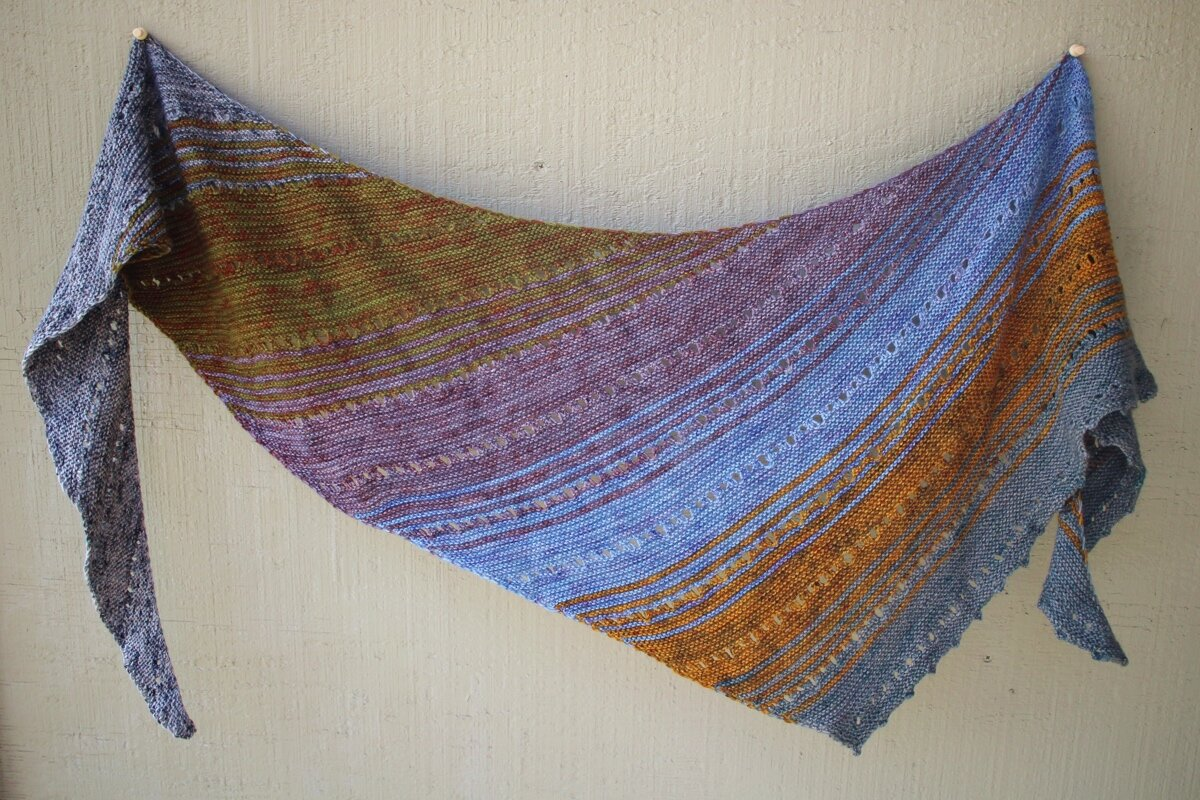 A finished Free Your Fade shawl hanging from a wall. #knitting #AndreaMowry  Shawl Parade | withwool.com