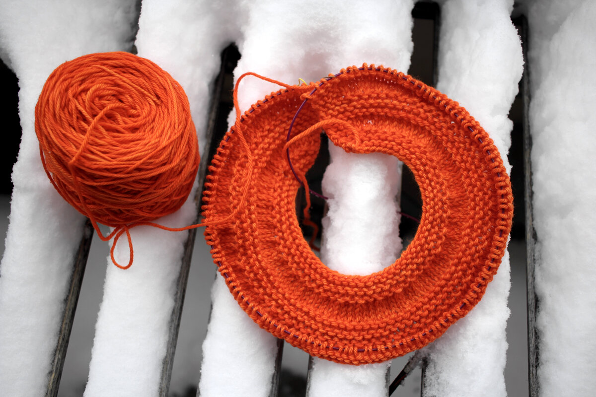 An orange ball of yarn and an in progress sweater yoke sit on a table covered in snow. #knitting  Sweater Weather || withwool.com