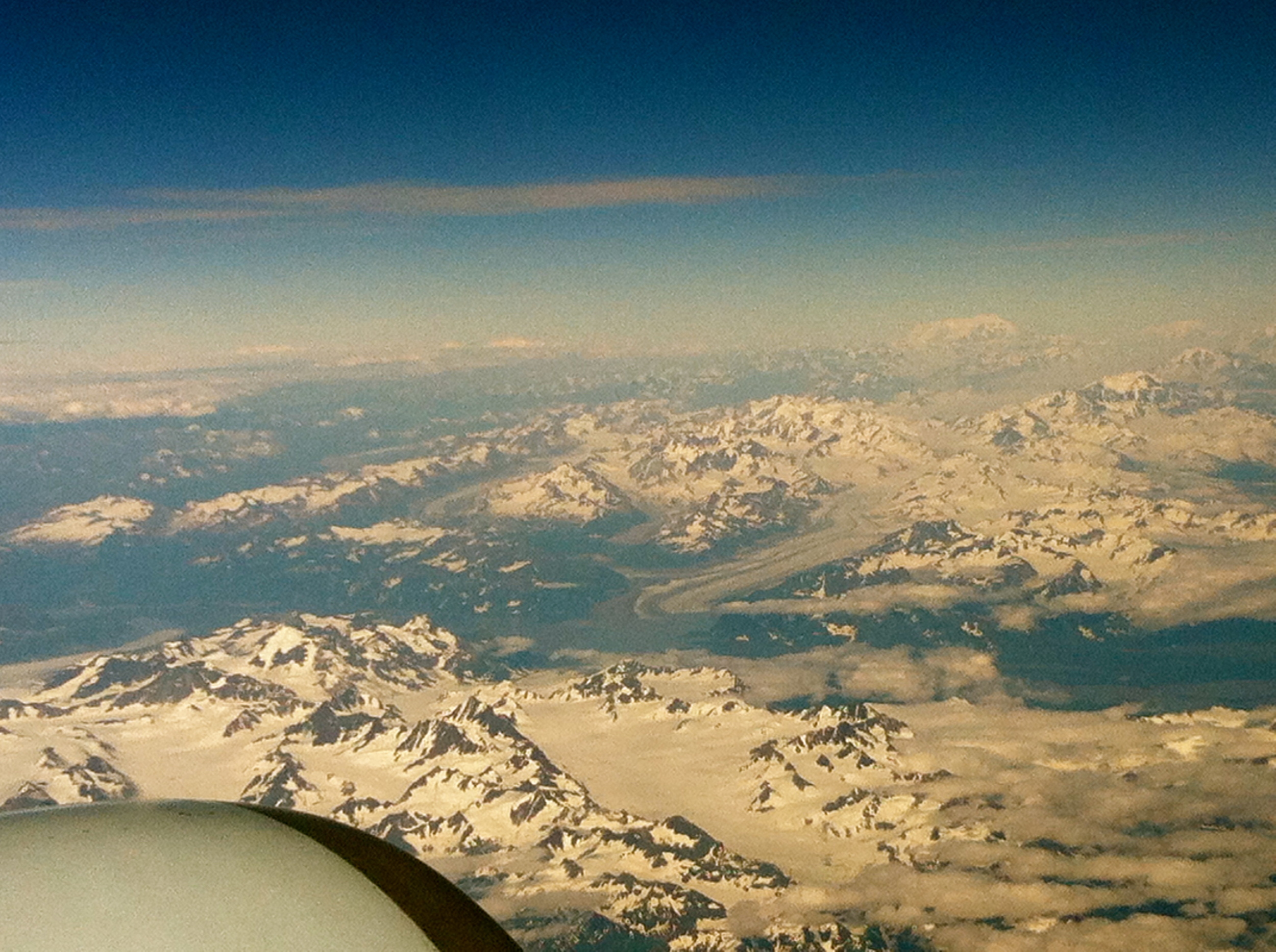 Looks kind of chilly down there! Checking out Alaska above the clouds.