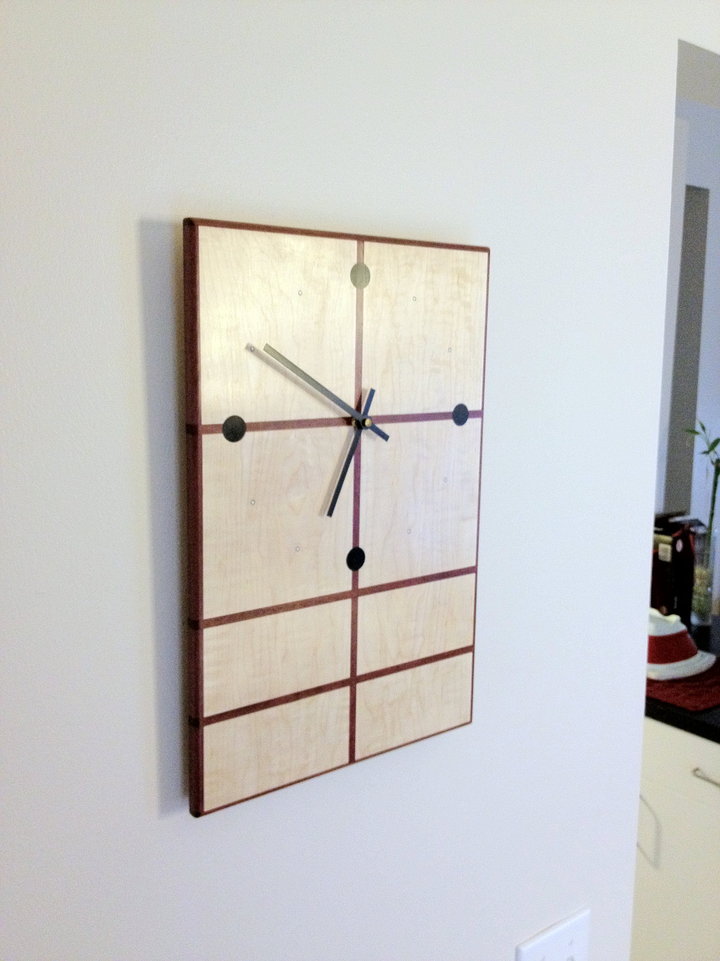 ​Clock #1: Curly maple and purpleheart rails with ebony plugs for the major hour markers.