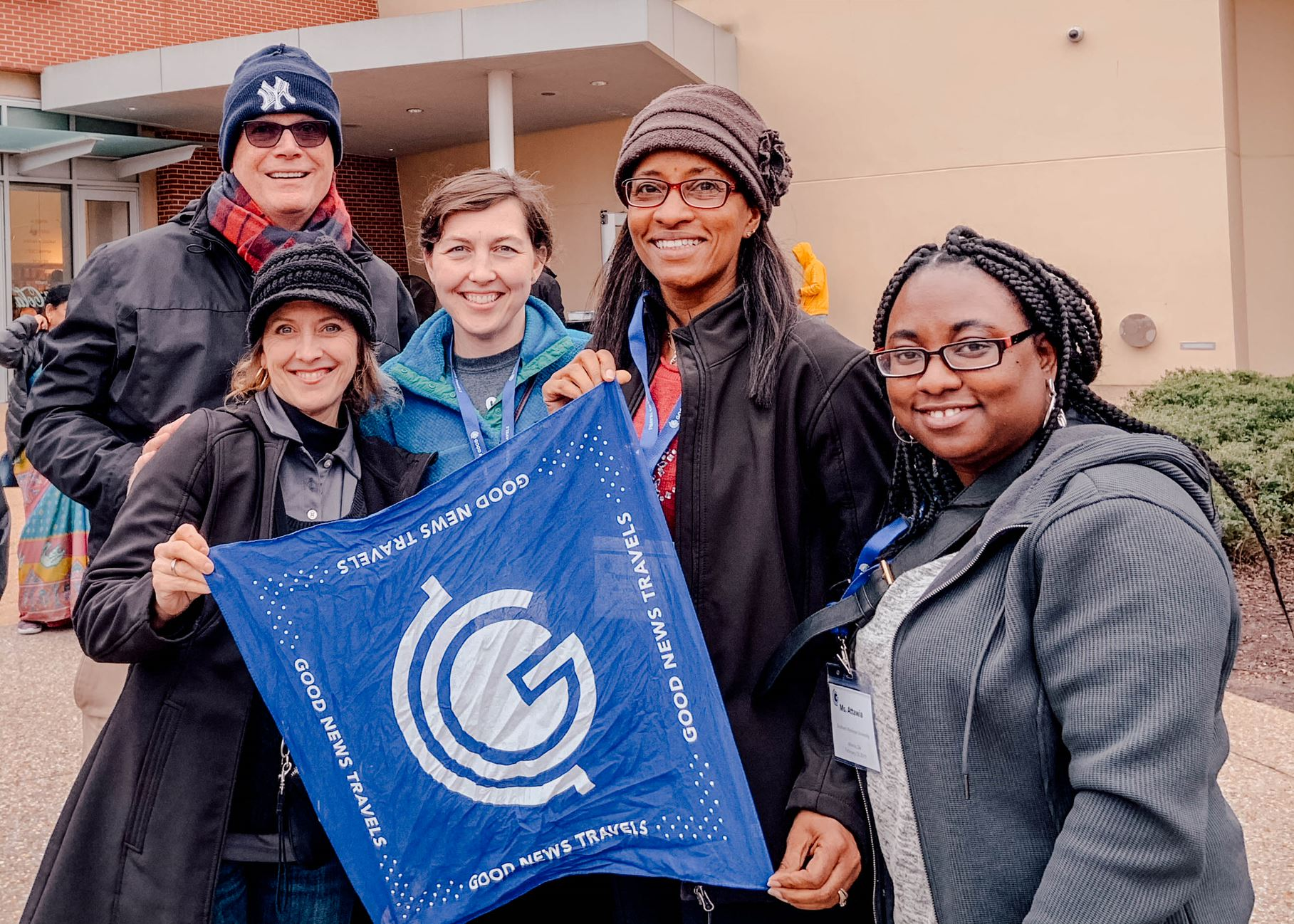 Group holding the Good News Travels flag