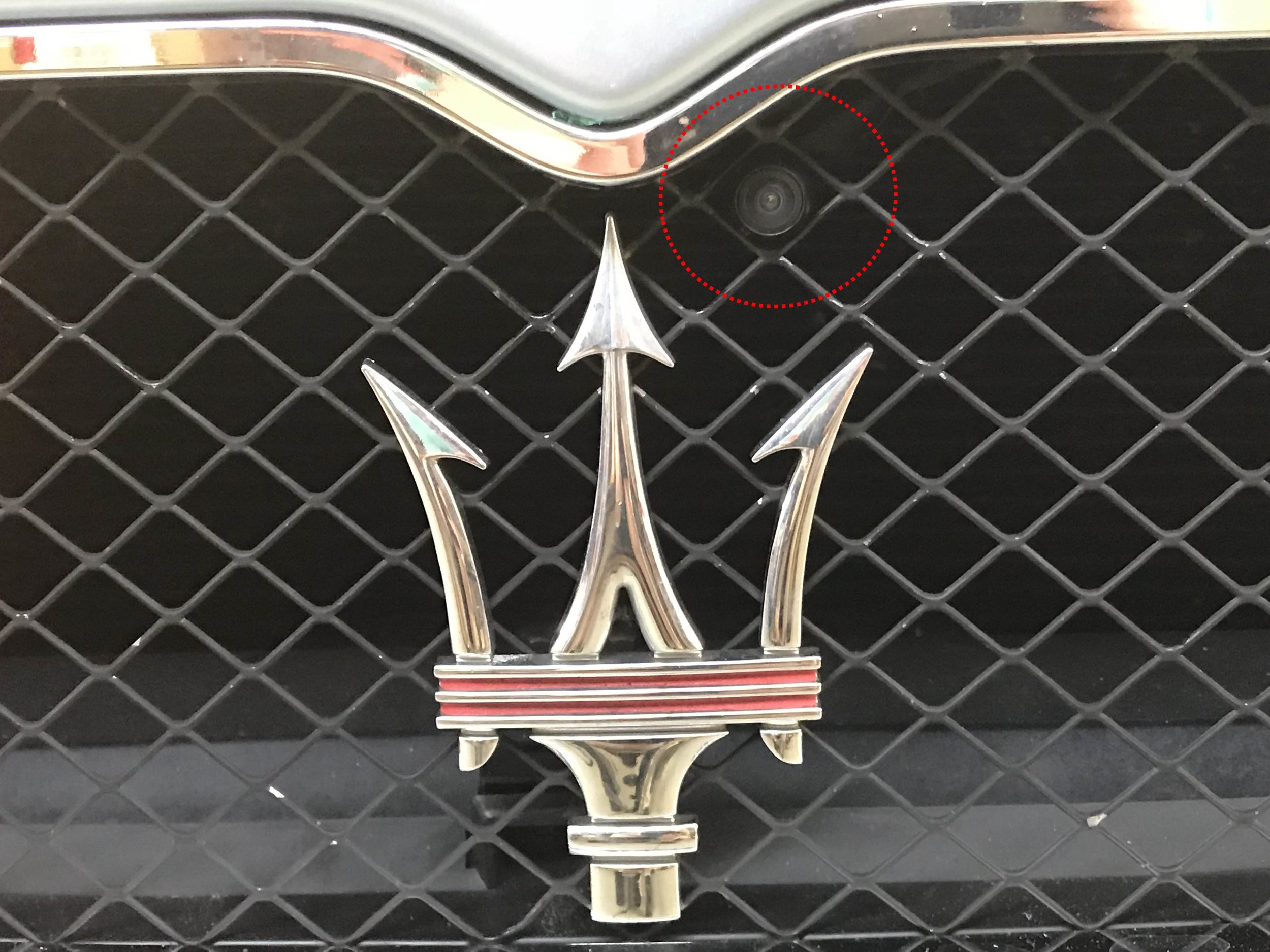 Highlighted in red above the trident in the grille, the camera looks straight out in front of the car without being noticeable