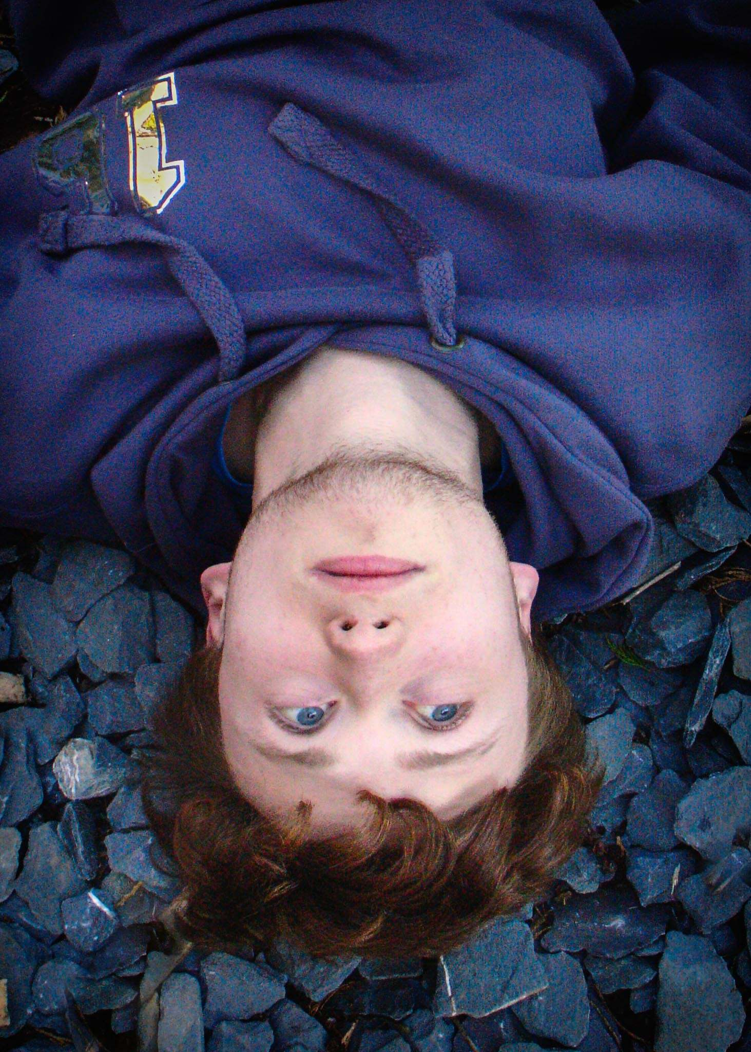 Title of Image:    Gulliver's Gravel  Description: My Brother is upside down and looks like his has a face upside down.  How did you take the shot? My brother sat on the swing and then leant backwards until he was upside down.  Then I took the photo with him looking upwards.  When you look at the photo what do you think?      I think of a hairy cheek man  How hard was it to take the shot?    It was easy because I just had to photograph him upside down.