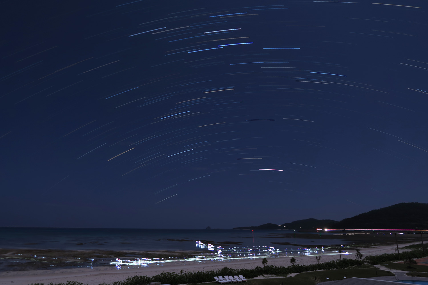 30 minute star trail exposure with people looking for crabs with flashlights at 2:00am.