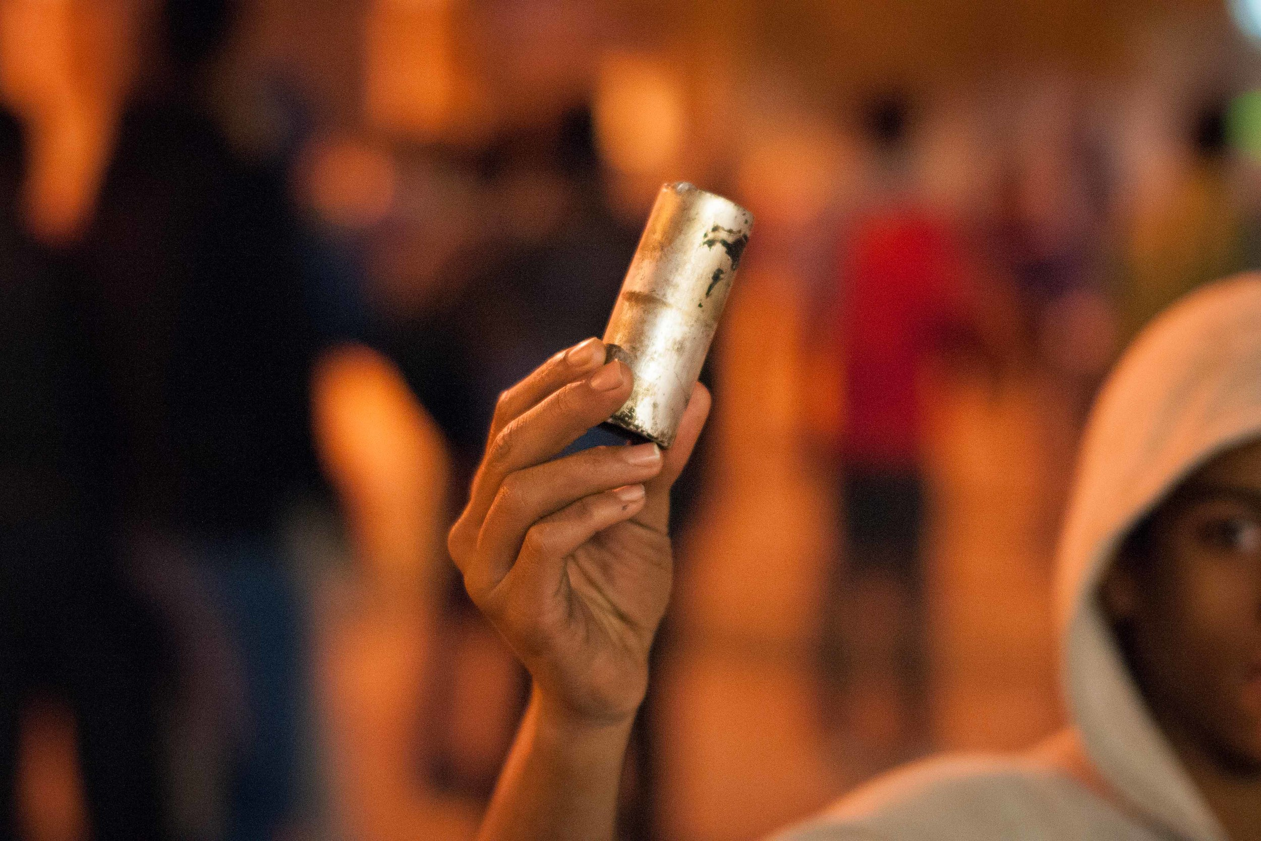A child holds up one of the canisters that had been shot from the police. The manufacture date for many of the canisters was 2012, meaning it is much more potent than last year's gas, but also dissipates quicker.