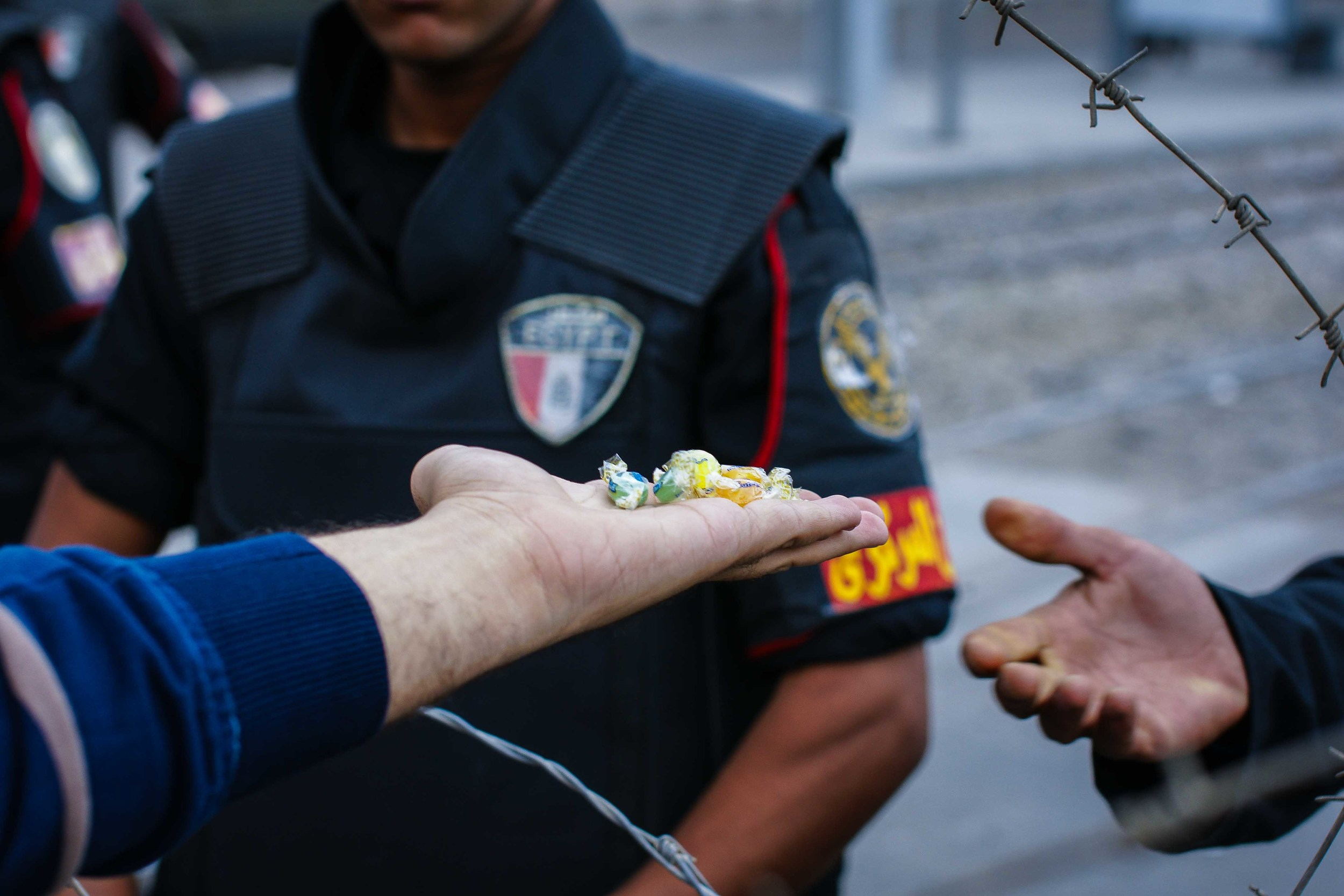 A protestor hands small candies through the barbed wire to a riot police officer. Candies, I might add, which the officer readily accepted.