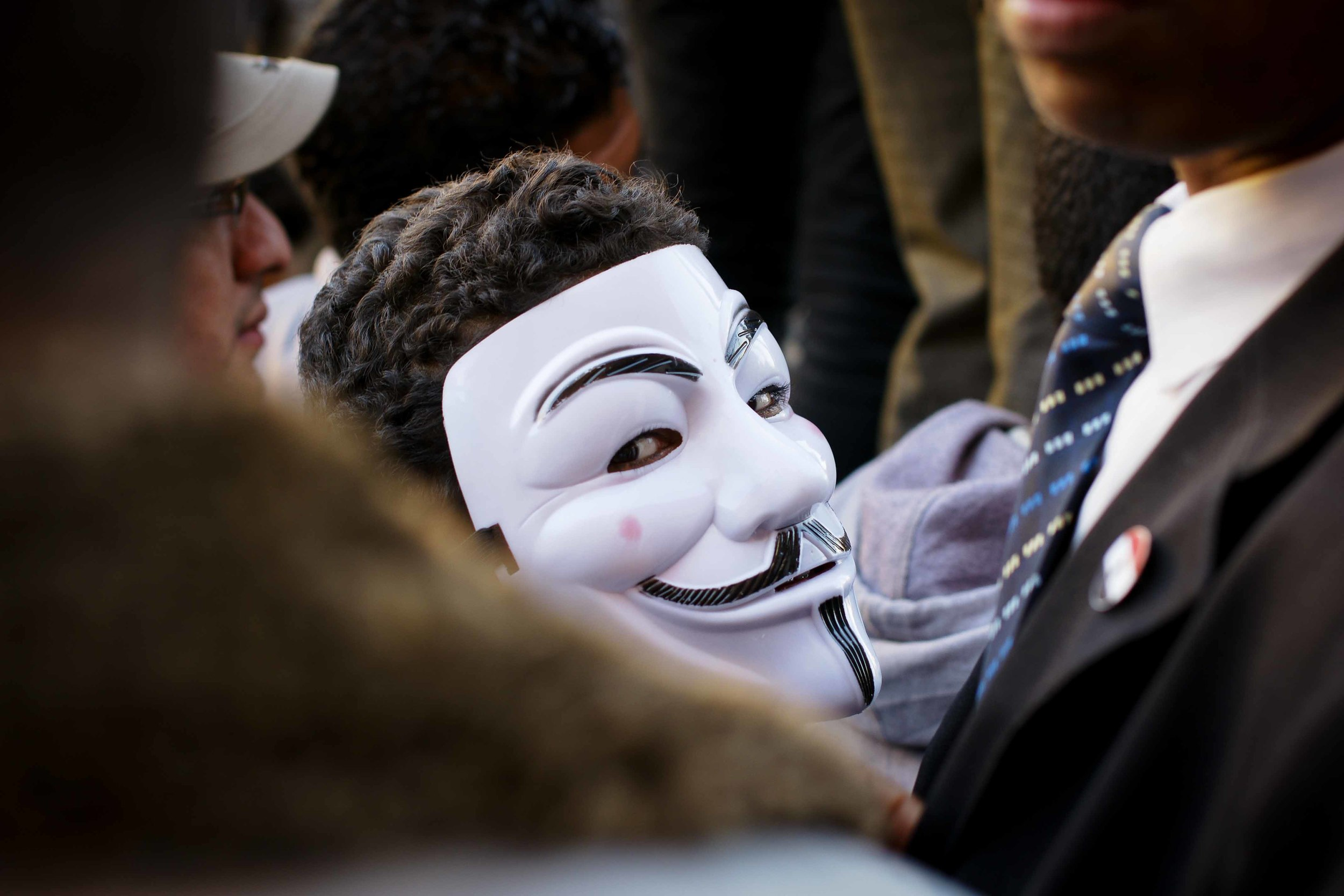 A protestor in a Guy Fawkes mask stands at the barricade erected by the military. Many protestors wear the masks, reminiscent of the movie 'V for Vendetta.'