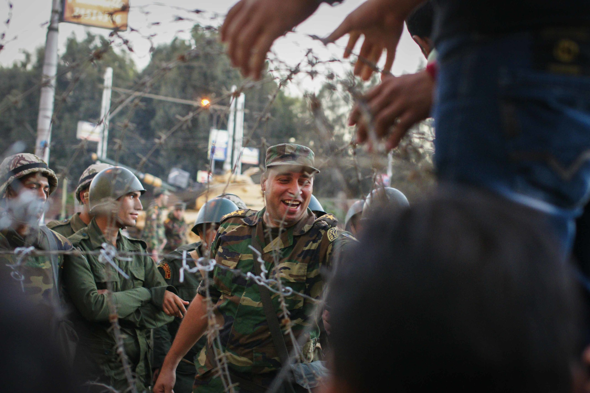 A member of the military jokes with a protestor as he is handed candy. In order to diffuse the tension, soldiers passed over Egyptian flags to the protestors, and protestors handed the soldiers candy or small items in return.