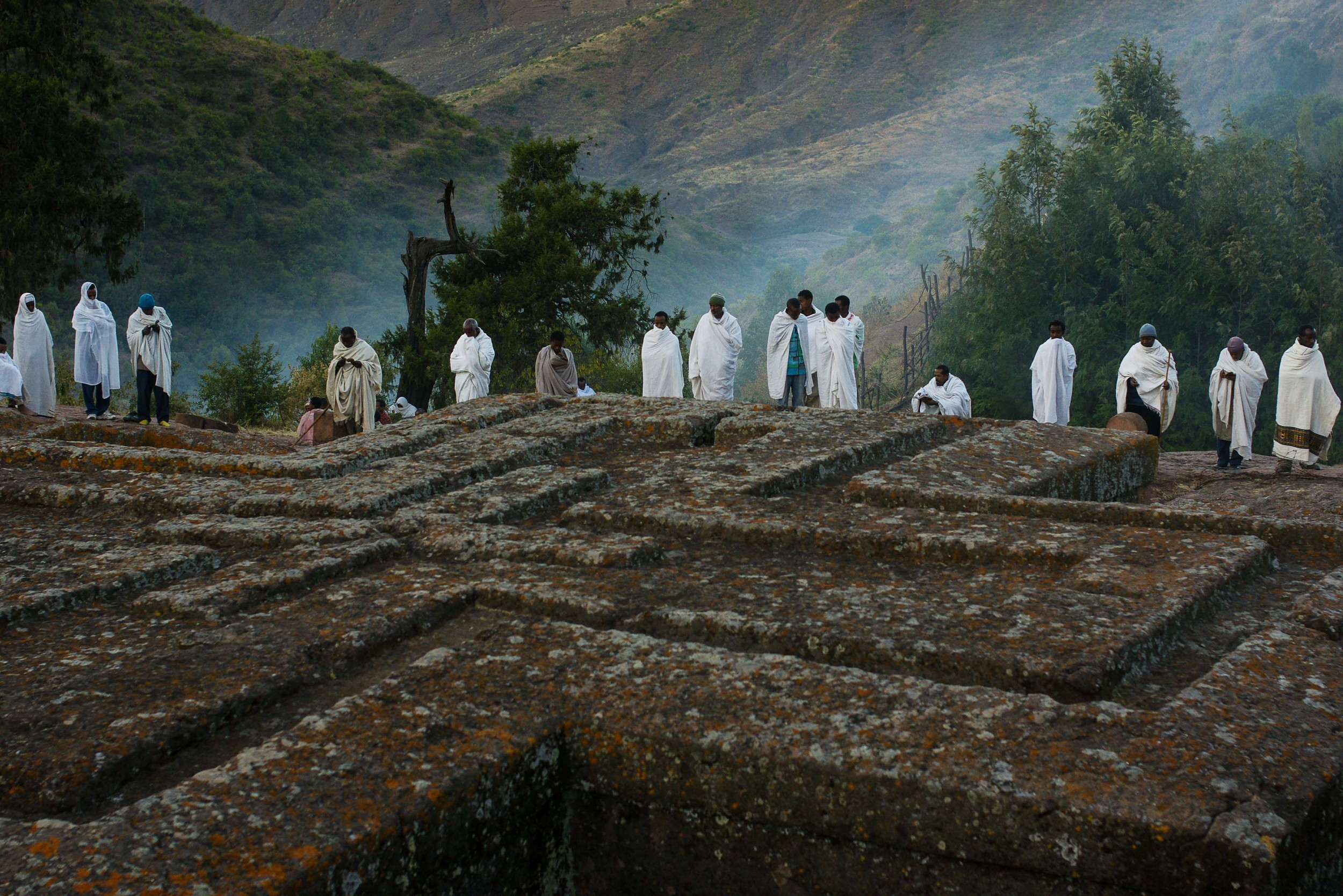 Perched high in the mountains of Northern Ethiopia, the small town of Lalibela is a place of pilgrimage during the time of Orthodox Christmas, and Ethiopian Christianity's second holiest site.Wrapped in shrouds of early morning mist and cotton, Ethiopian Orthodox Christians stand in prayer at the edge of Bet Giyorgis, the rock church carved to resemble a cross.