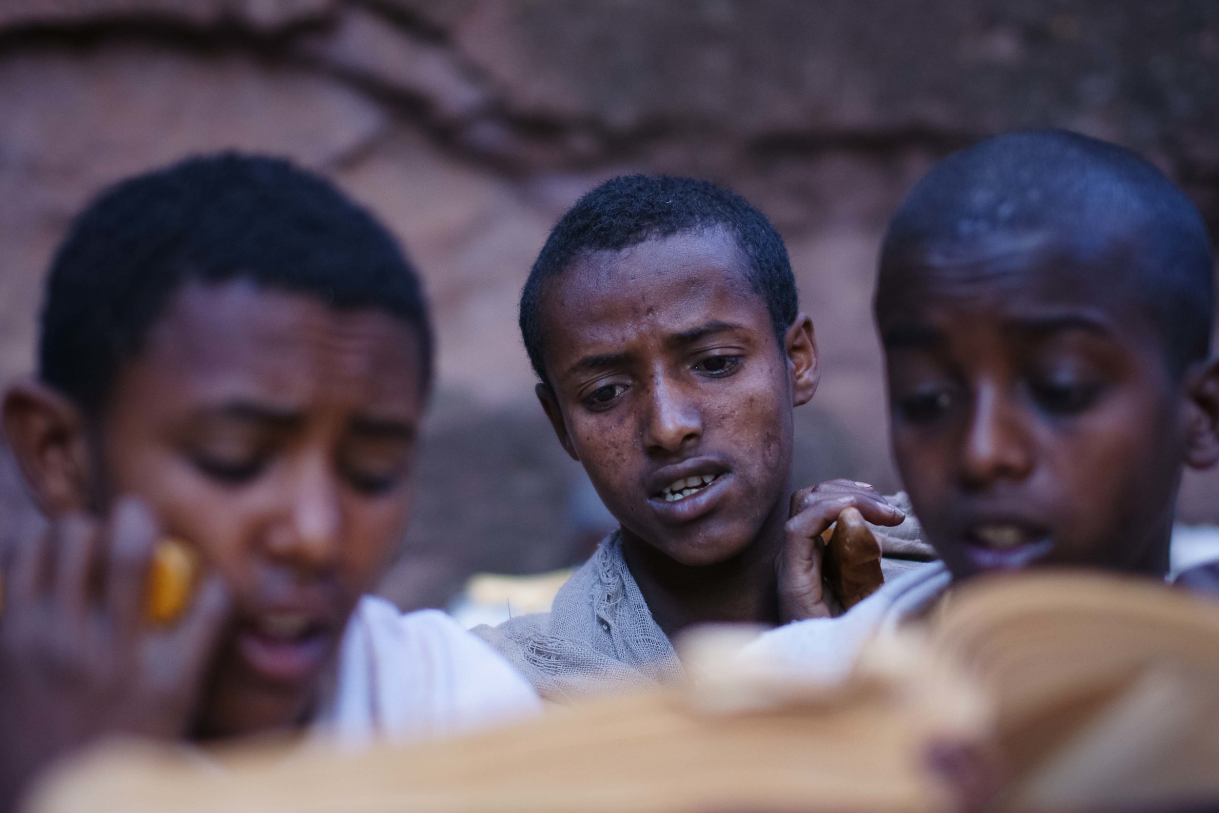A group of young boys read from the Bible as priests sing around them.
