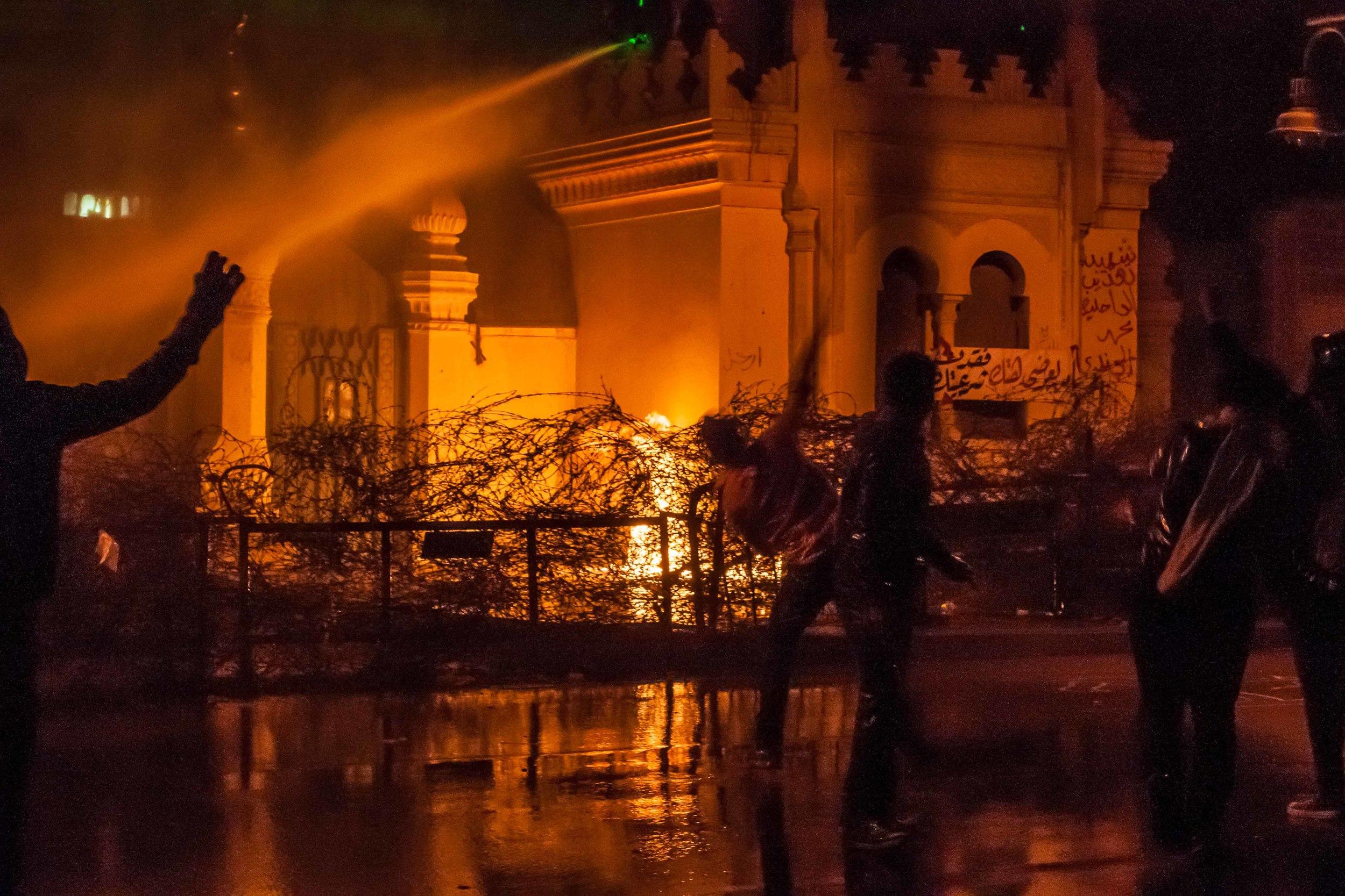 Protestors hurl rocks at the palace as water canons fire at protestors.