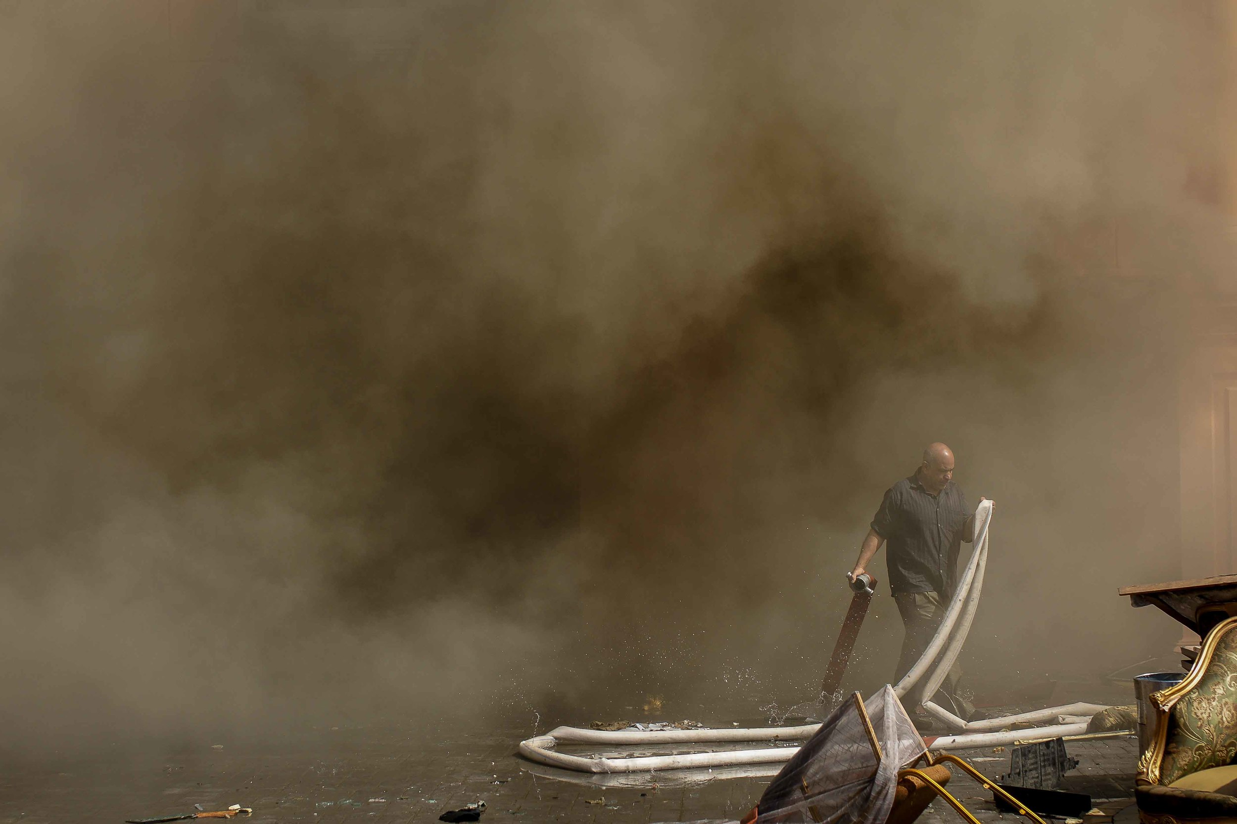 Workers tried in vain to contain the blaze as thick smoke poured out of the building.