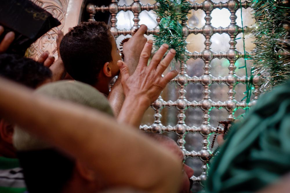 Worshippers clamour to touch the tomb of Sayeda Zeinab.