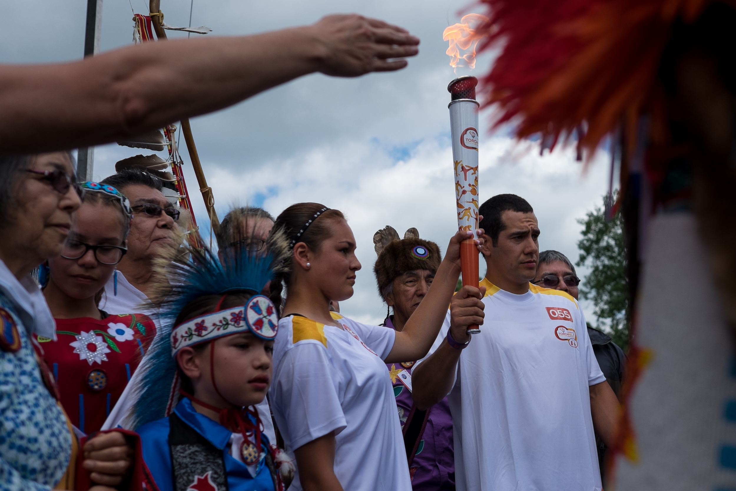 Ryann Laforme (centre) holds the Pan Am torch as during a celebration in New Credit. Charlie Bittern, Bill Chippeway, Charlie Nelson and Bill Merasty stand behind her.