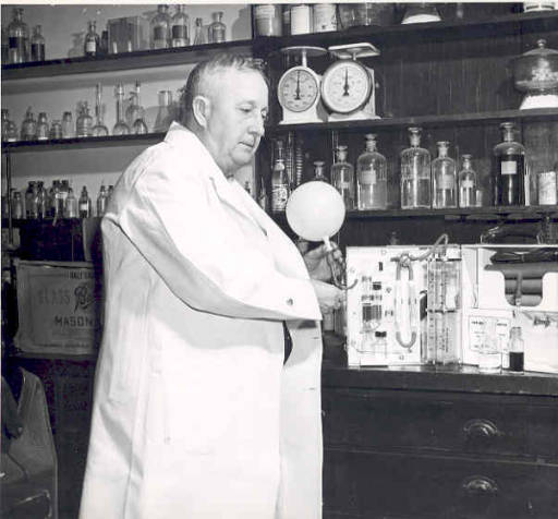 """Dr. Rolla Harger displaying his """"Drunkometer,"""" first practical apparatus used to determine blood-alcohol levels by analyzing breath. IUPUI Digital Collections (n.d.)"""